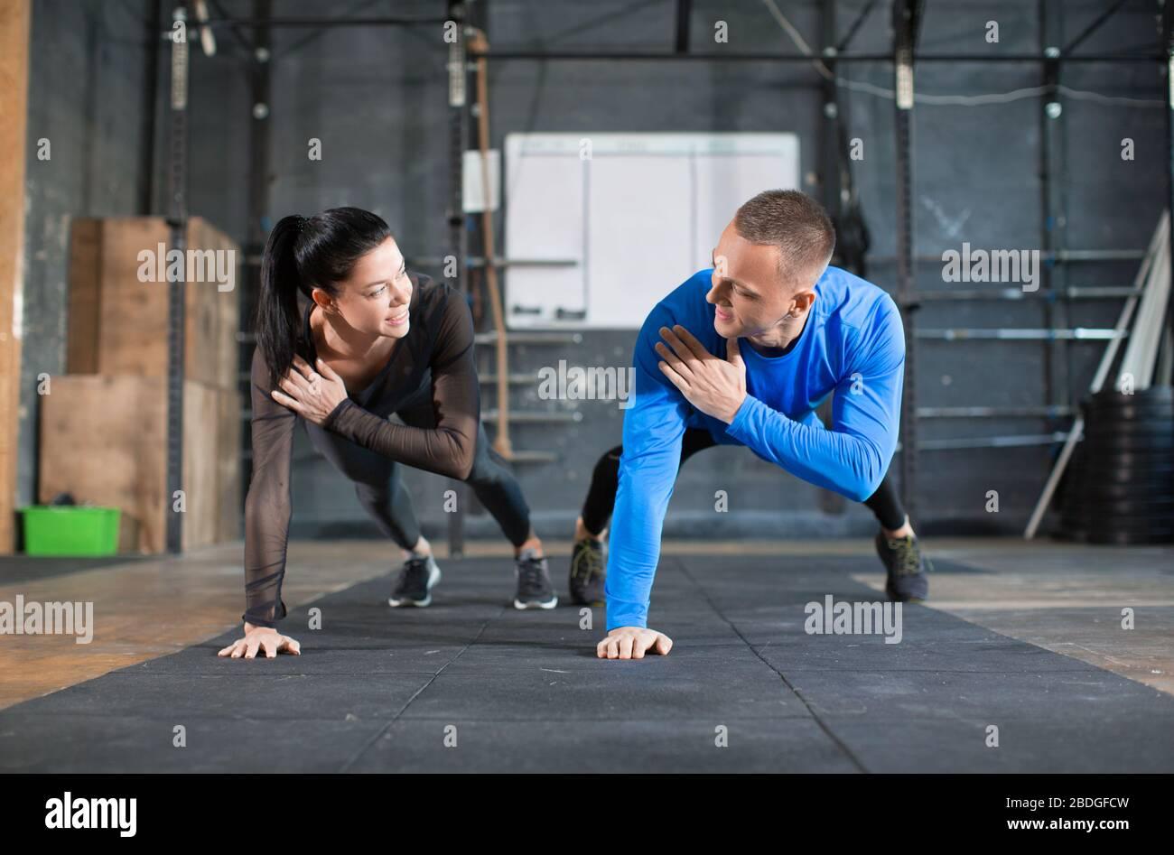 Des poussettes hommes et femmes à l'entraînement dans la salle de gym. Concept de sport, de fitness et de mode de vie sain. Banque D'Images