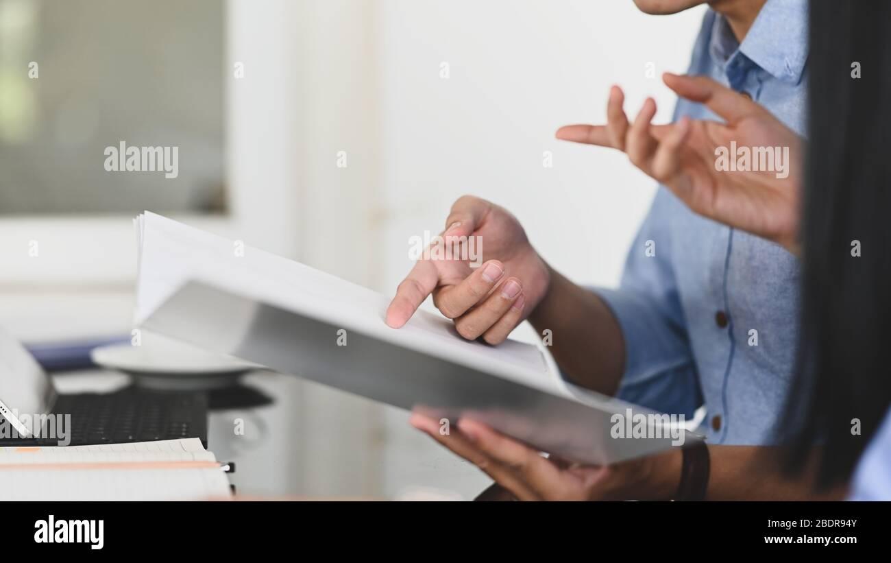 Image rognée de l'équipe de développement commercial discutant/réunion sur le résultat de son bénéfice commercial tout en tenant un fichier de document et en étant assis en mode Banque D'Images