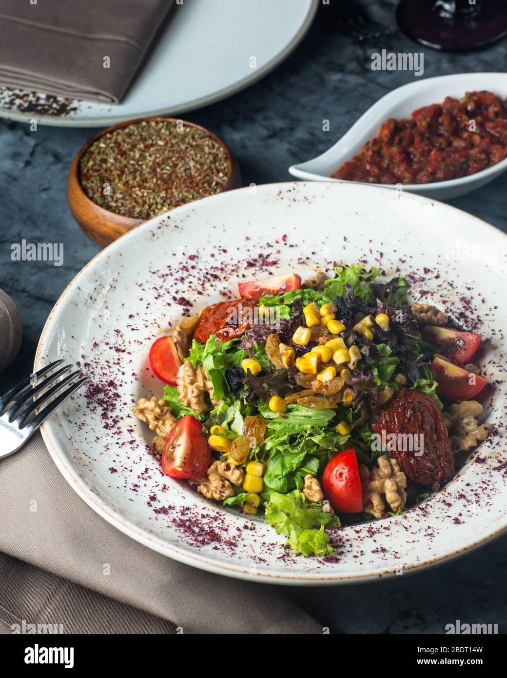 une assiette de salade verte avec du maïs de tomates de laitue et du raisin Banque D'Images