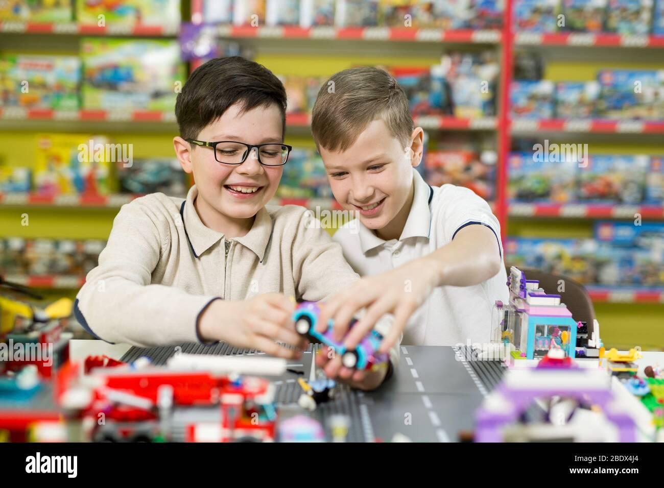 Les enfants jouent dans le concepteur à la table. Deux garçons jouent avec des blocs de plastique de couleur dans le centre de jeu, l'école Banque D'Images