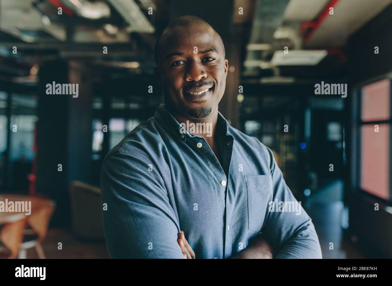 Homme d'affaires confiant au bureau. Un homme africain debout avec ses bras a croisé regarder la caméra et sourire. Banque D'Images