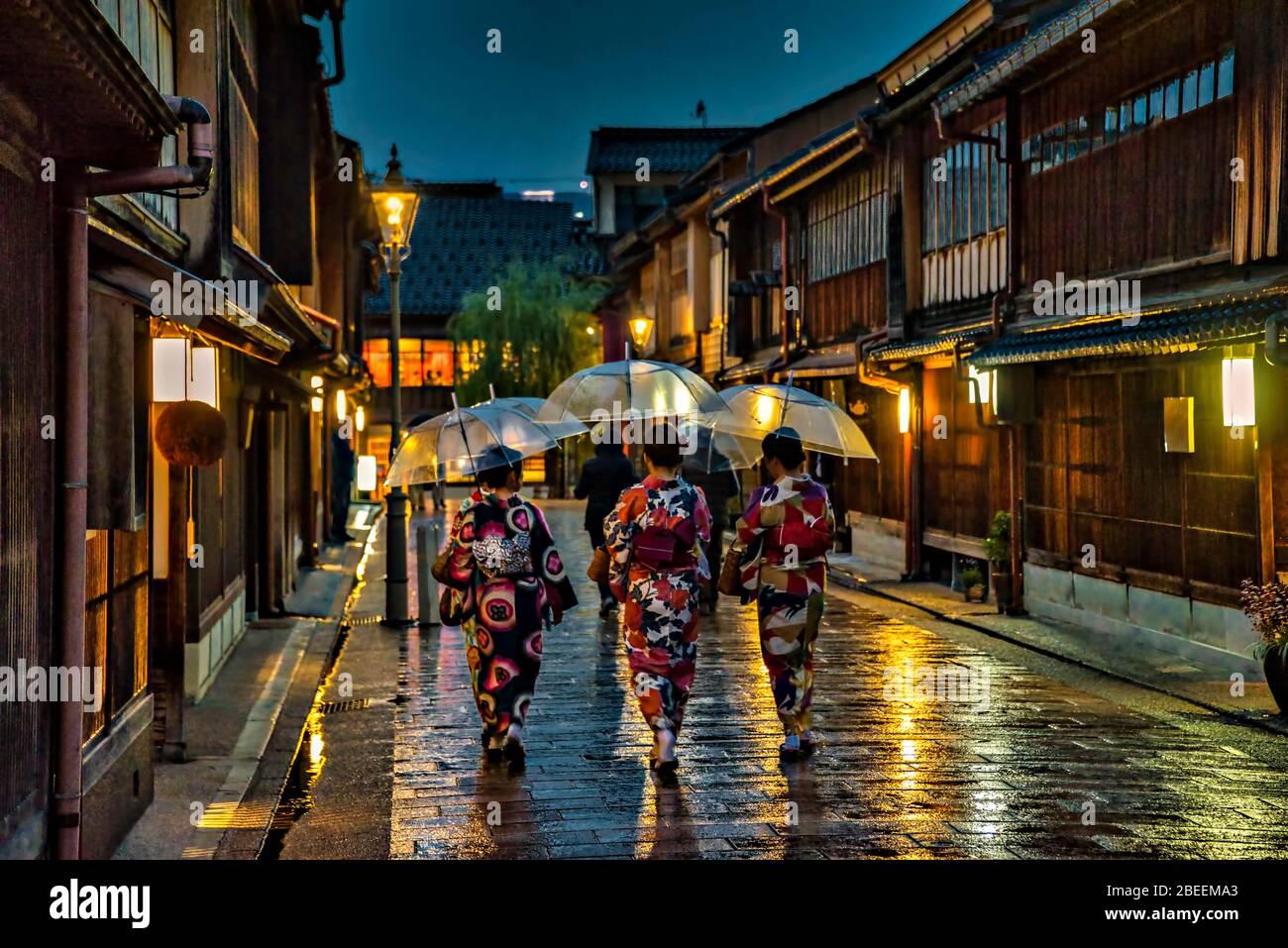 Les femmes dans les kimono traditionnels marchant dans le quartier de Higashi Chaya la nuit sous la pluie, Kanazawa, Japon. Banque D'Images