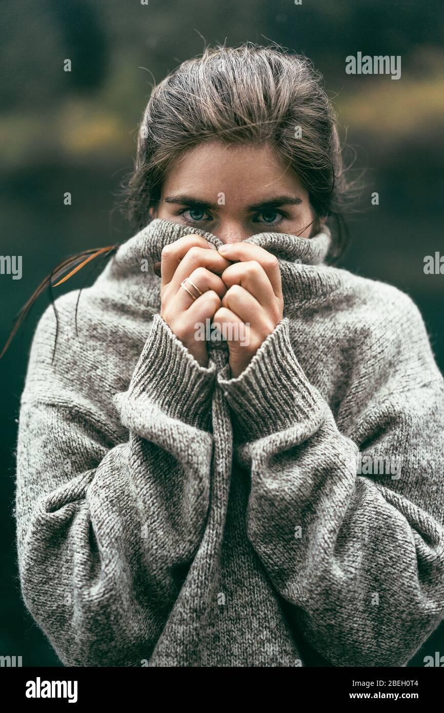 Portrait d'une jeune femme couvrant le visage avec un pull confortable Banque D'Images
