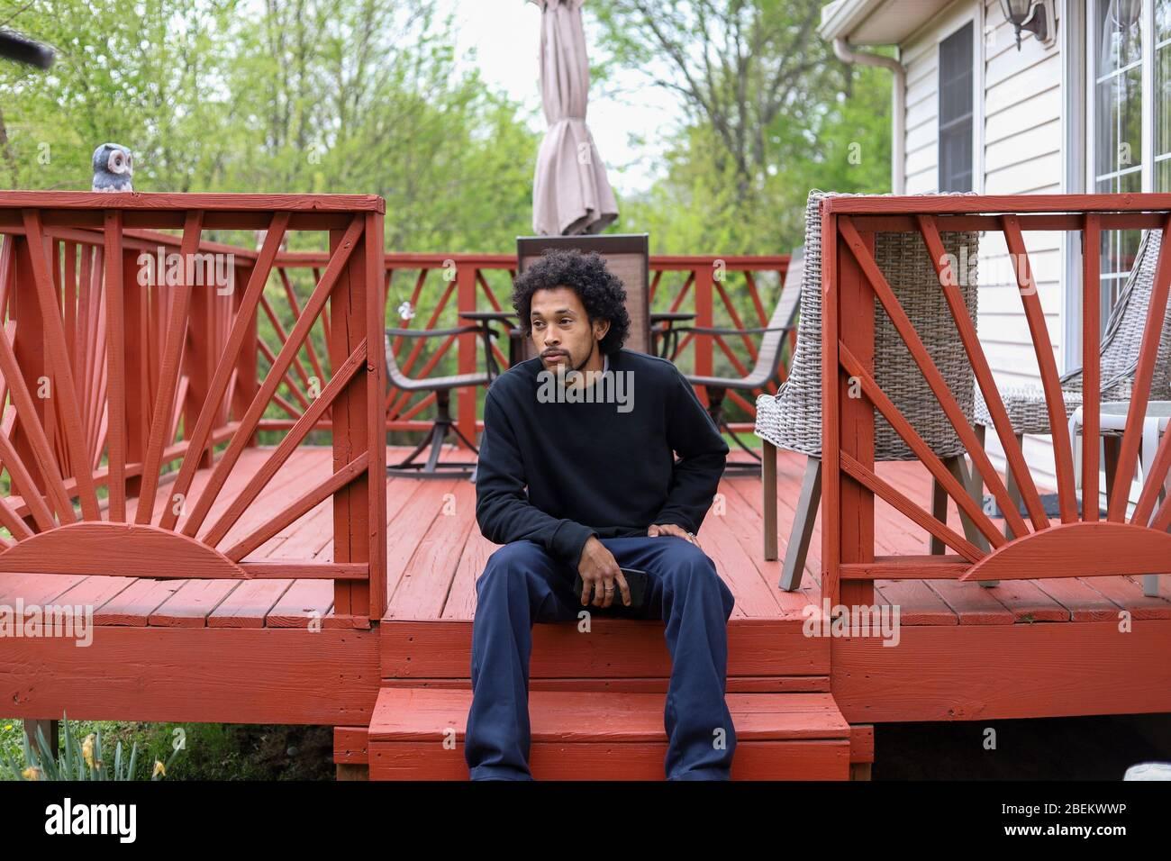 Un portrait d'un homme afro-américain sur son téléphone portable à l'extérieur et triste Banque D'Images
