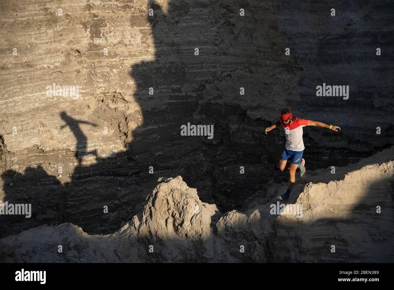Un sentier d'homme qui descend à travers une crête sur un terrain sablonneux Banque D'Images