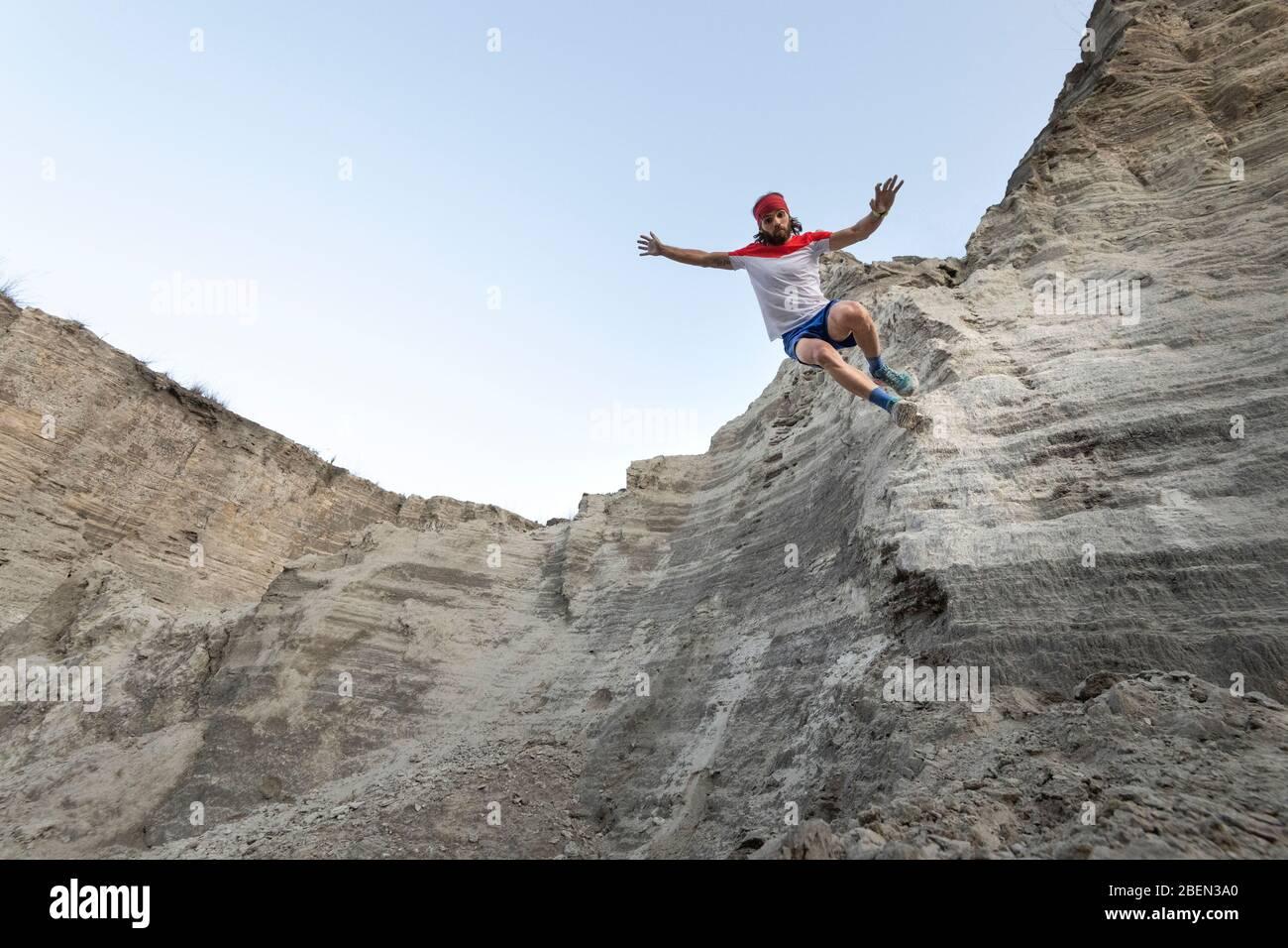Un homme s'entête sur un mur très raide à un vieux gaspillage de sable minier Banque D'Images