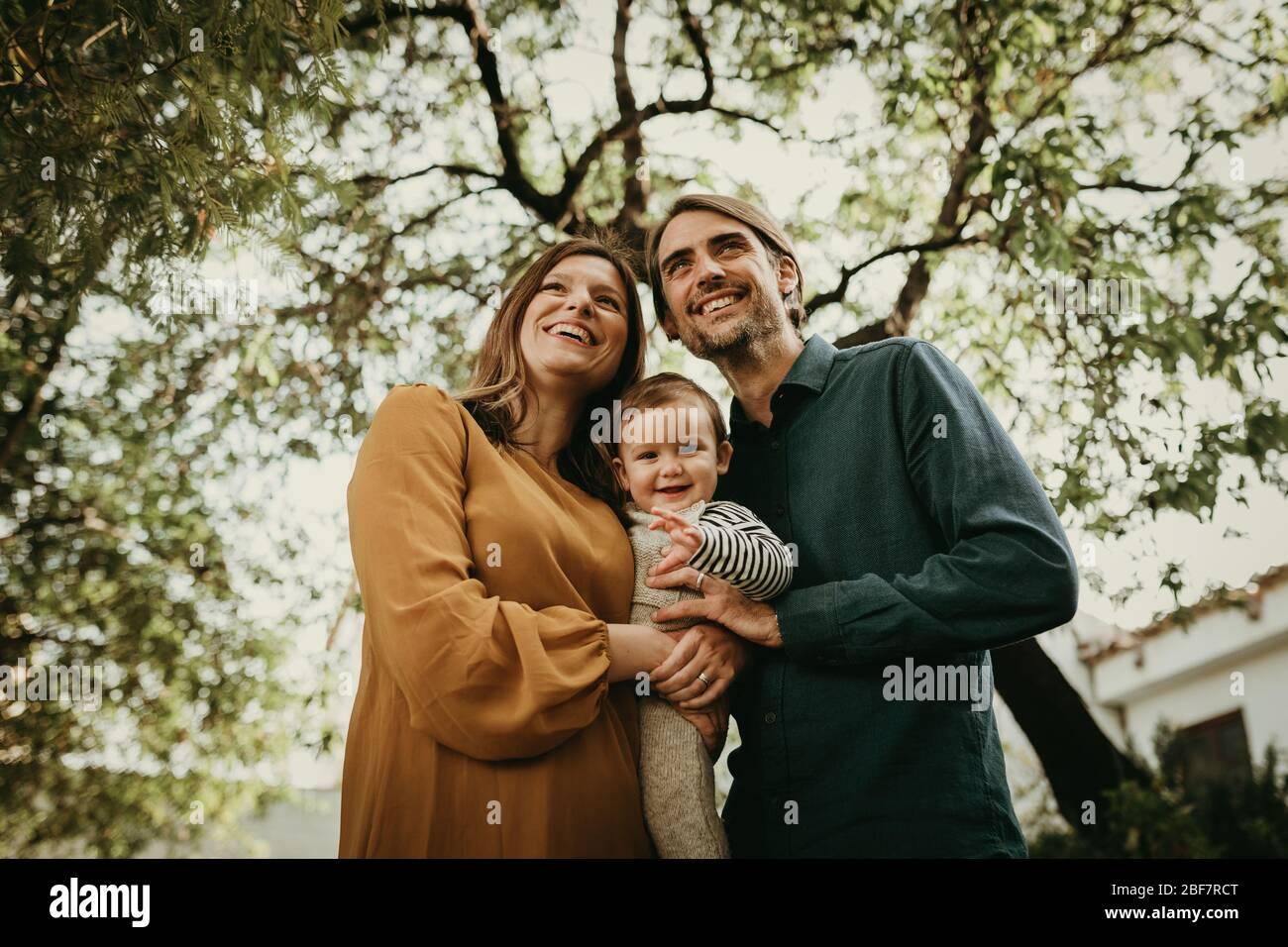 Couple charmant et souriant se posant dans le jardin avec leur fils de bébé dans les bras. Banque D'Images
