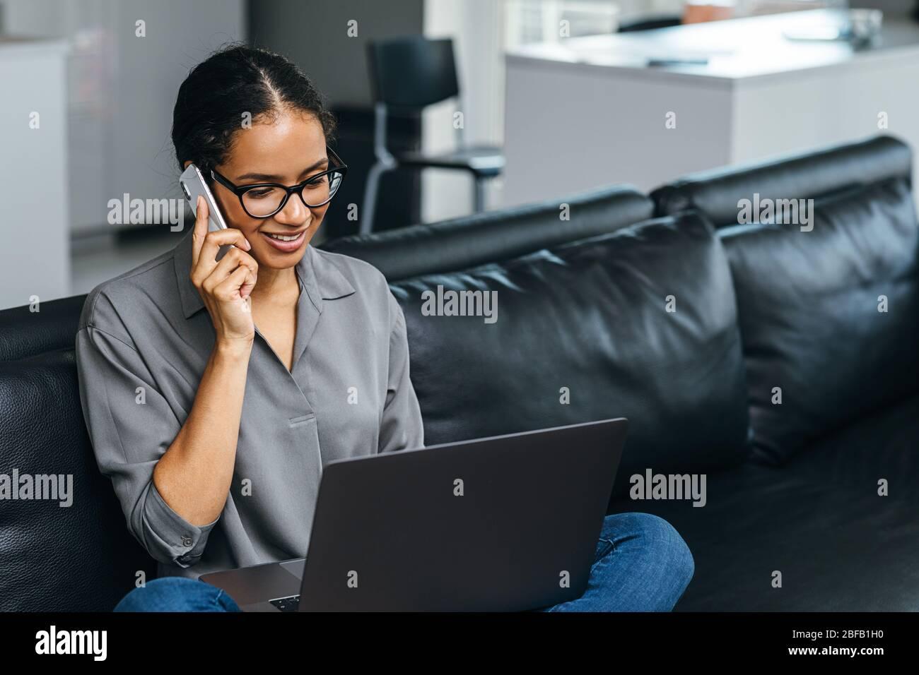 Belle femme utilisant un smartphone ayant un appel téléphonique de son appartement. Femme d'affaires en train de discuter assis sur un canapé. Banque D'Images