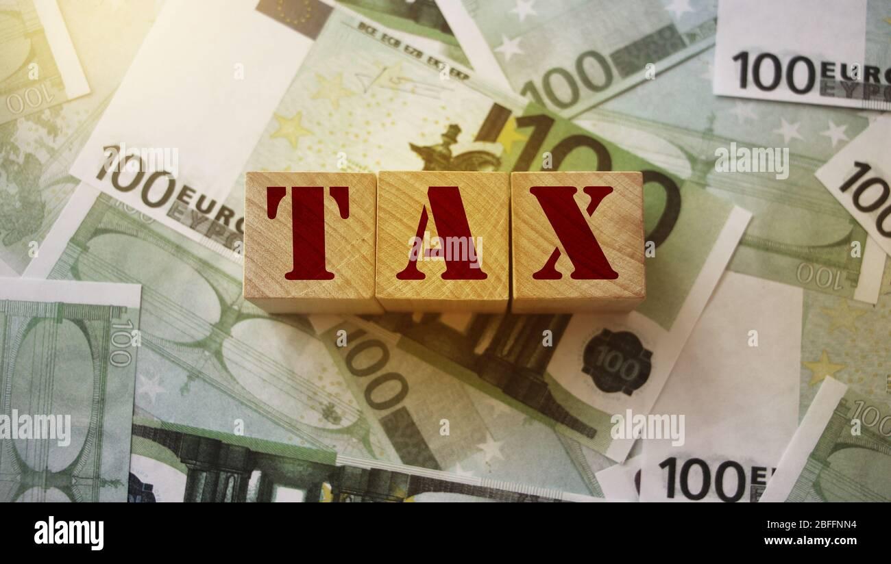 Blocs en bois avec taxe de mot sur 100 billets en euros. Concept comptable de financement des impôts Banque D'Images