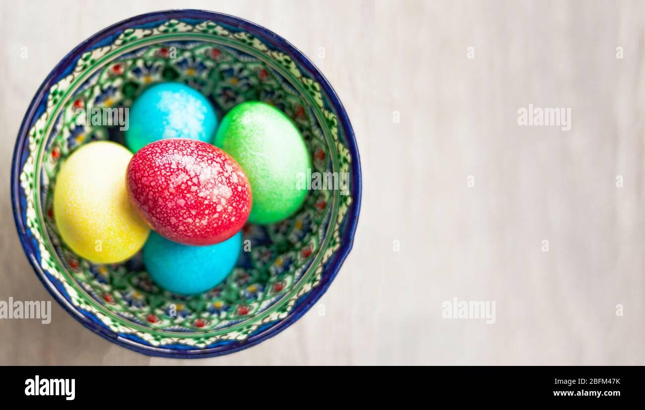 Œufs de Pâques colorés dans un bol sur fond blanc naturel en bois. Vue de dessus. Pose plate. Banque D'Images
