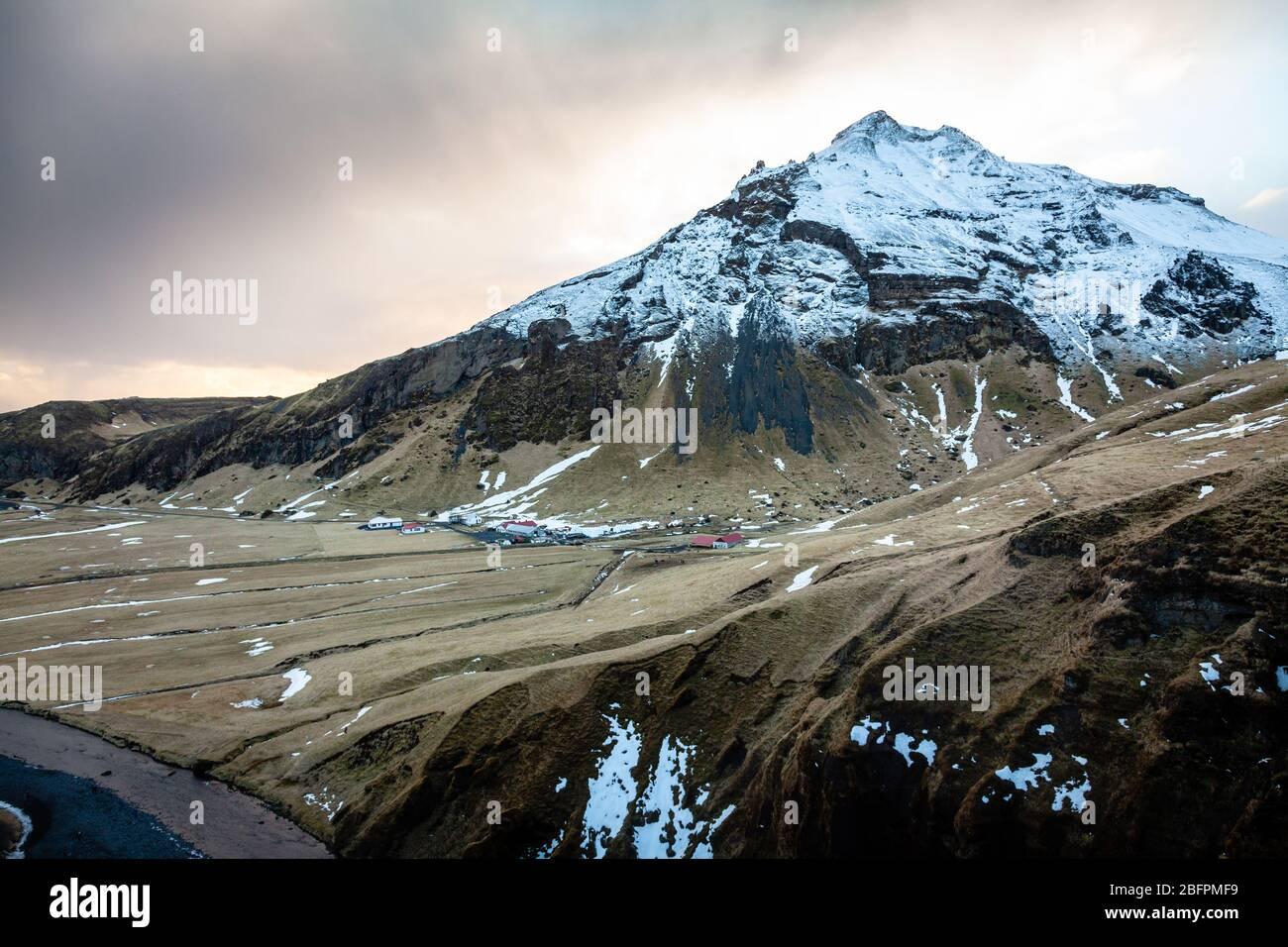 La vue depuis le sommet de la cascade de Skógafoss (Skogarfoss ou Skogafoss) en Islande en hiver avec une montagne enneigée derrière Banque D'Images