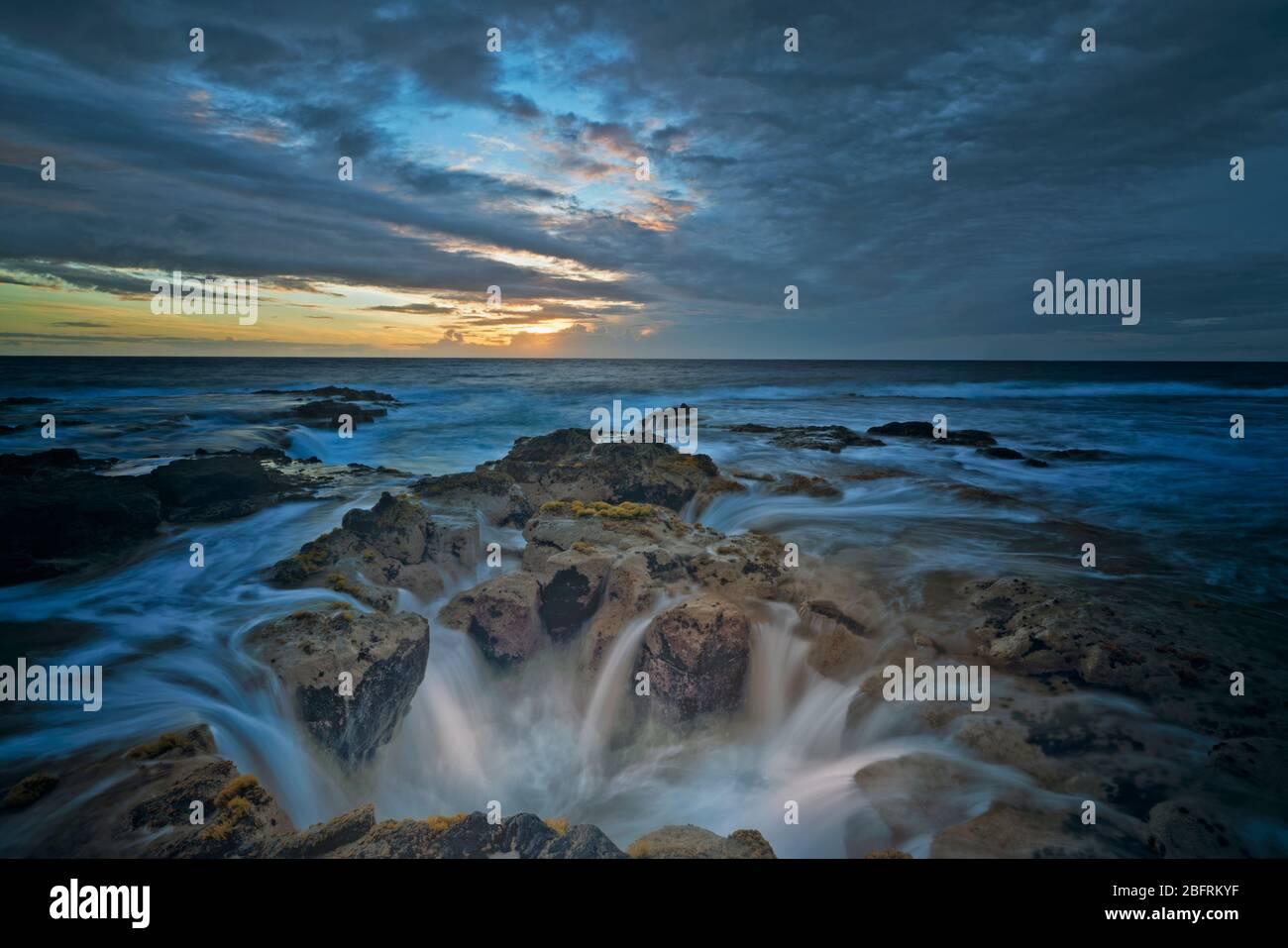 Les dernières couleurs du coucher du soleil illuminent le tube de lave connu sous le nom de Pele's well près de Wawaloli Beach sur la Grande île d'Hawaï. Banque D'Images