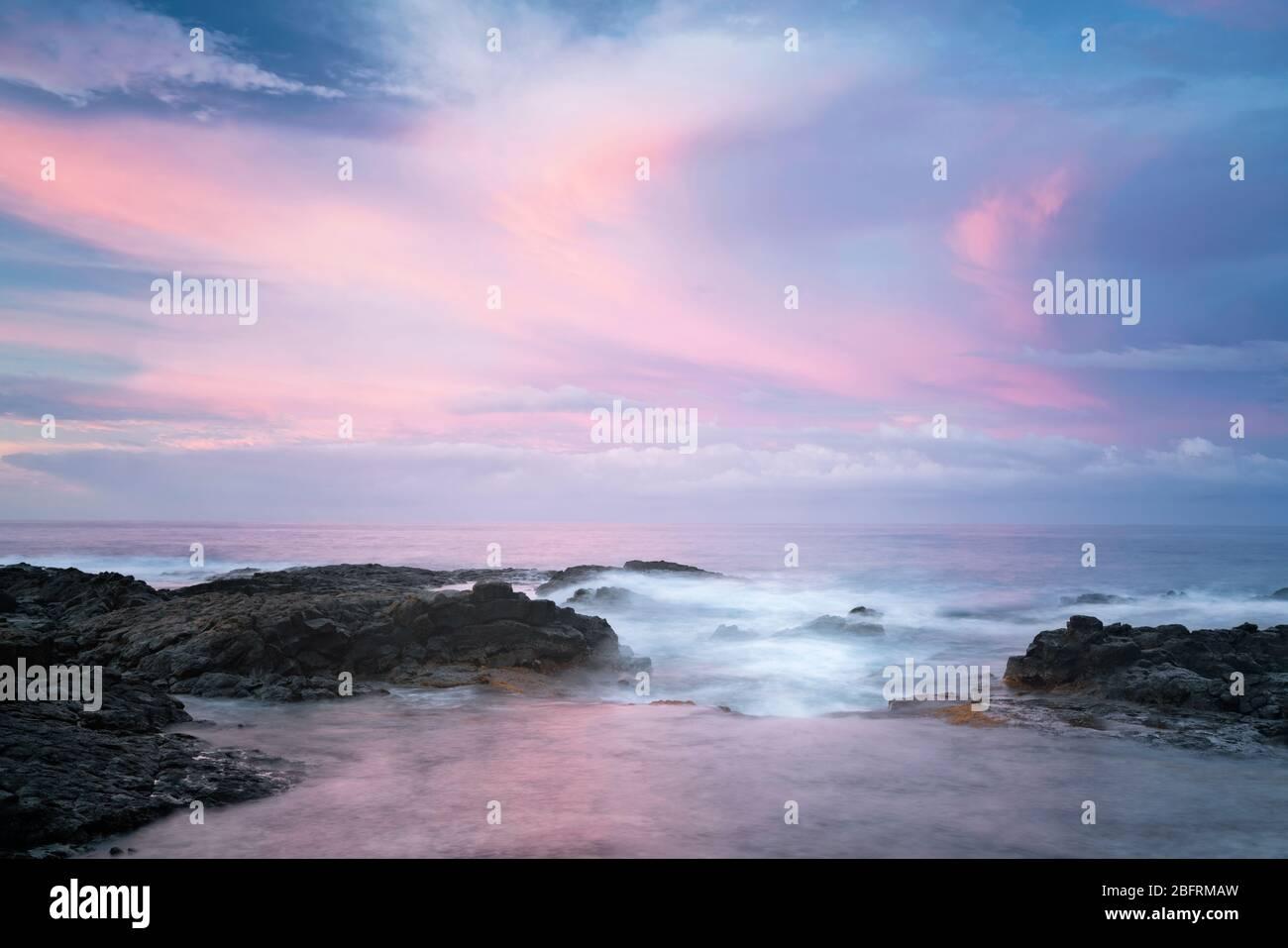 Les couleurs du lever du soleil illuminent le ciel sur le littoral de lave au parc de la plage de Kohanaiki le long de la côte de Kona sur la Grande île d'Hawaï. Banque D'Images