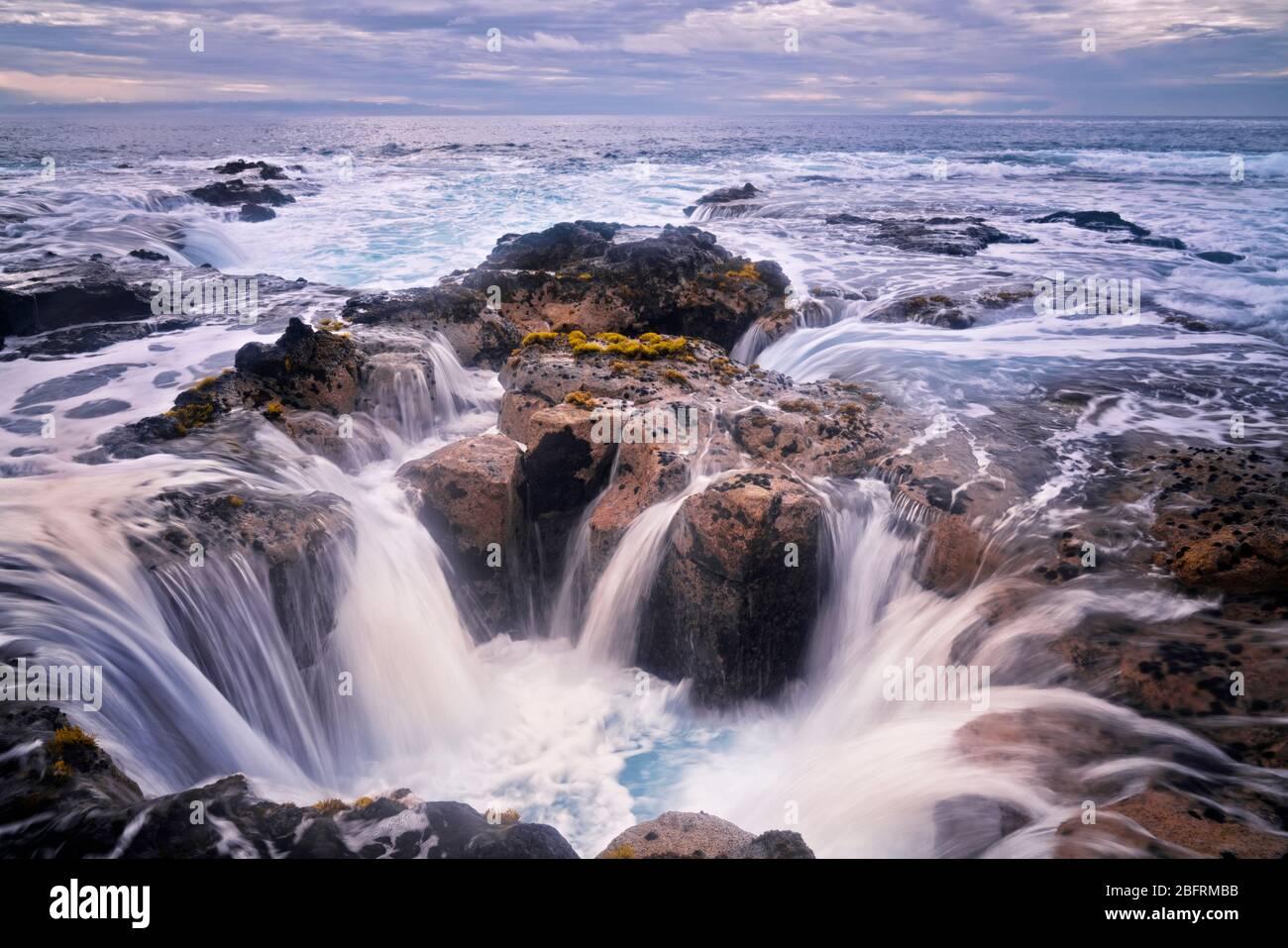La marée haute du soir se verse dans le tube de lave connu sous le nom de Pele's well près de Wawaloli Beach sur la Big Island d'Hawaï. Banque D'Images