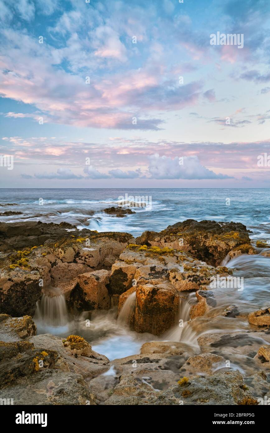 Les couleurs du lever du soleil illuminent le ciel au-dessus du tube de lave connu sous le nom de Pele bien le long de la côte de Kona sur la Grande île d'Hawaï. Banque D'Images