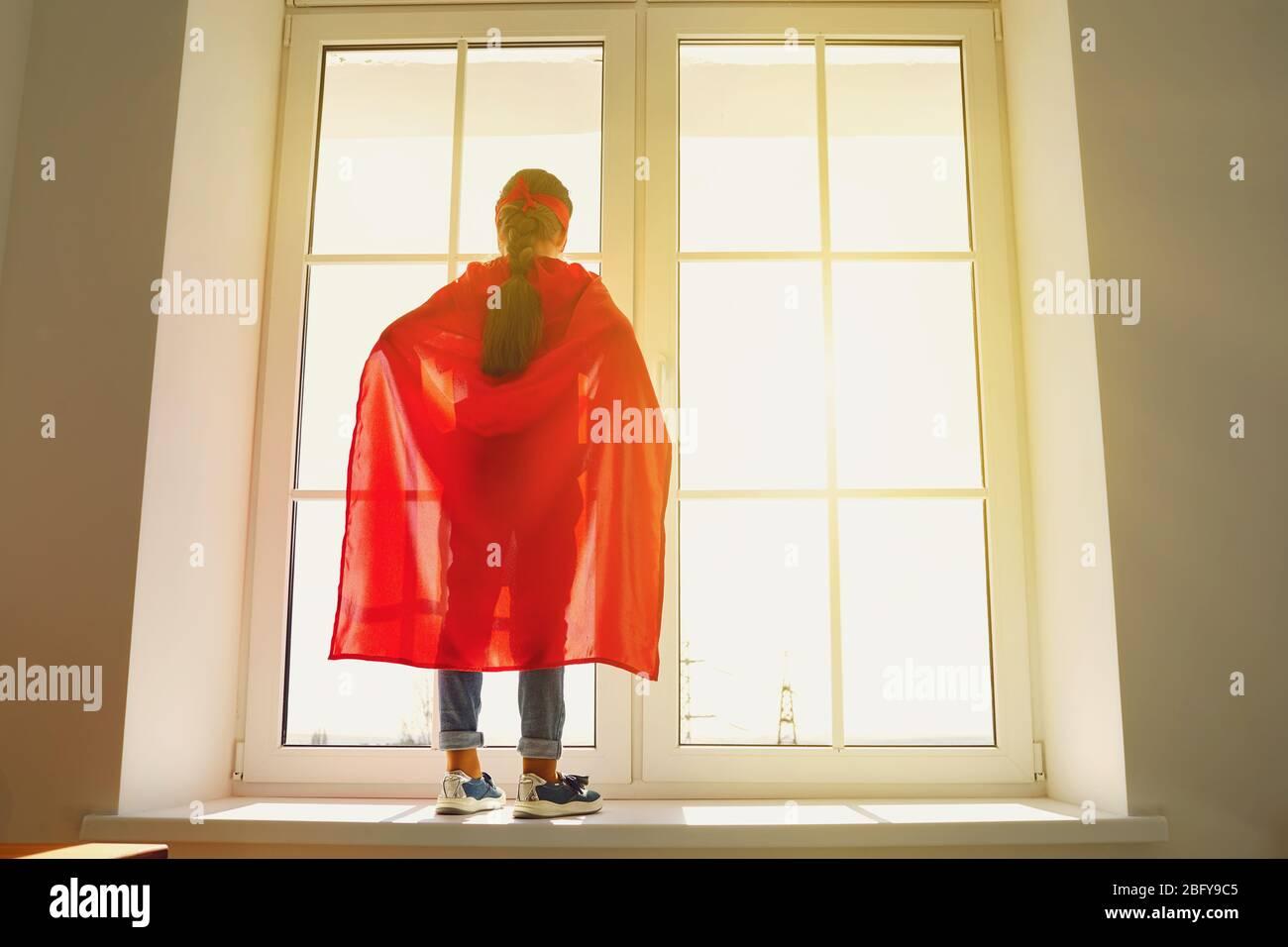 Fille enfant dans un costume de super-héros debout sur l'arrière-plan d'une fenêtre avec lumière du soleil regardant des rêves à la fenêtre Banque D'Images