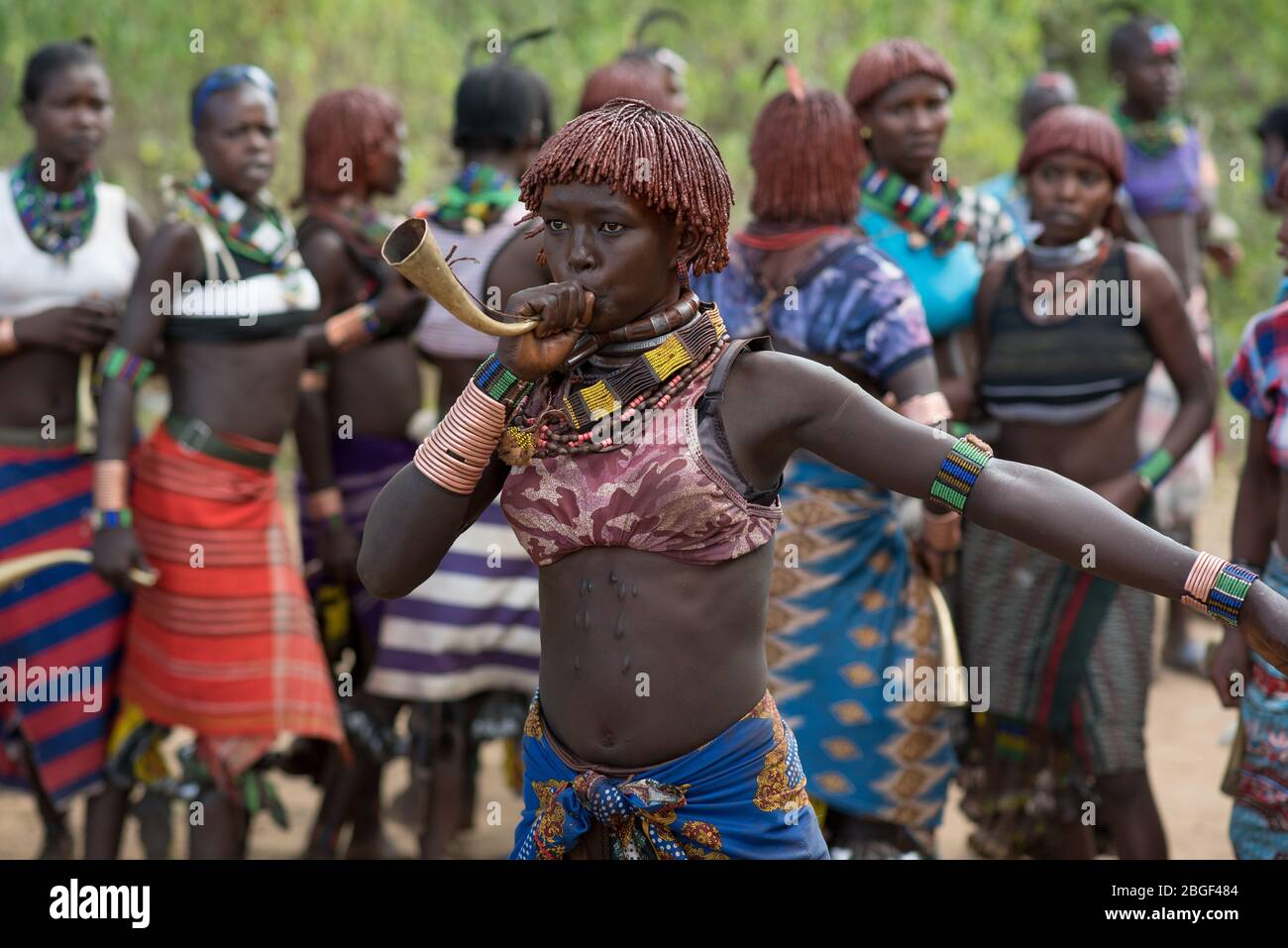 Les femmes dansent les cornes de laiton au groupe ethnique de la tribu de Morsi à l'âge de la cérémonie de saut à taureaux, Jenka, Ethiopie. Banque D'Images