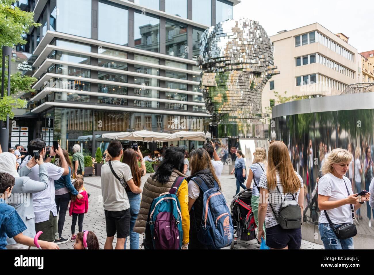Les gens, touristes regardant le chef de Franz Kafka connu sous le nom de Statue de Kafka sculpture extérieure par David Cerny, installé à l'extérieur des magasins Quadrio Banque D'Images