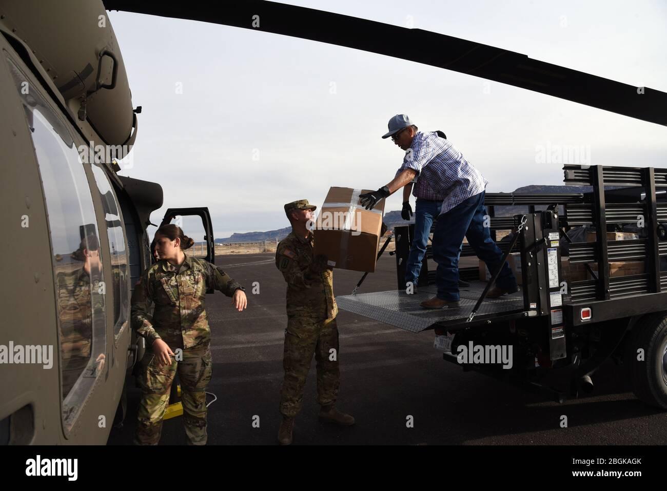 2 e lieutenant, Maram Sweis, officier des opérations médicales de la Garde nationale de l'Arizona et Sgt. Jonathan Atcitty, chef d'équipage de la Garde nationale de l'Arizona et personnel de l'hôpital Kayenta, chargent l'équipement médical de protection personnelle d'un UH-60 Blackhawk dans un camion le 31 mars 2020, à Kayenta, Ariz. la Garde nationale de l'Arizona a volé des EPI médicaux à l'hôpital local en réponse à COVID-19. La Garde de l'Arizona a réagi au pays dans des situations d'urgence comme la sécurité de l'aéroport après le 11 septembre 2011, le Monument Fire en 2011, l'ouragan Harvey en 2017 et les inondations de Havasupai en 2018 (États-Unis Photo de la Garde nationale aérienne par Tech. SG Banque D'Images