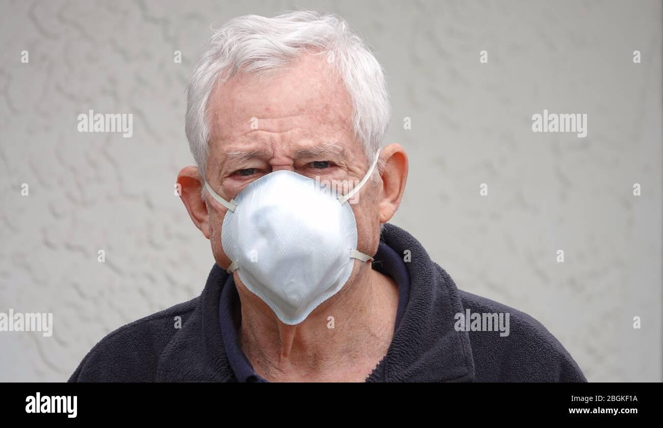 Homme caucasien âgé de 80 ans, âgé de plus en plus de difficulté, portant un masque facial pour se protéger du coronavirus Banque D'Images