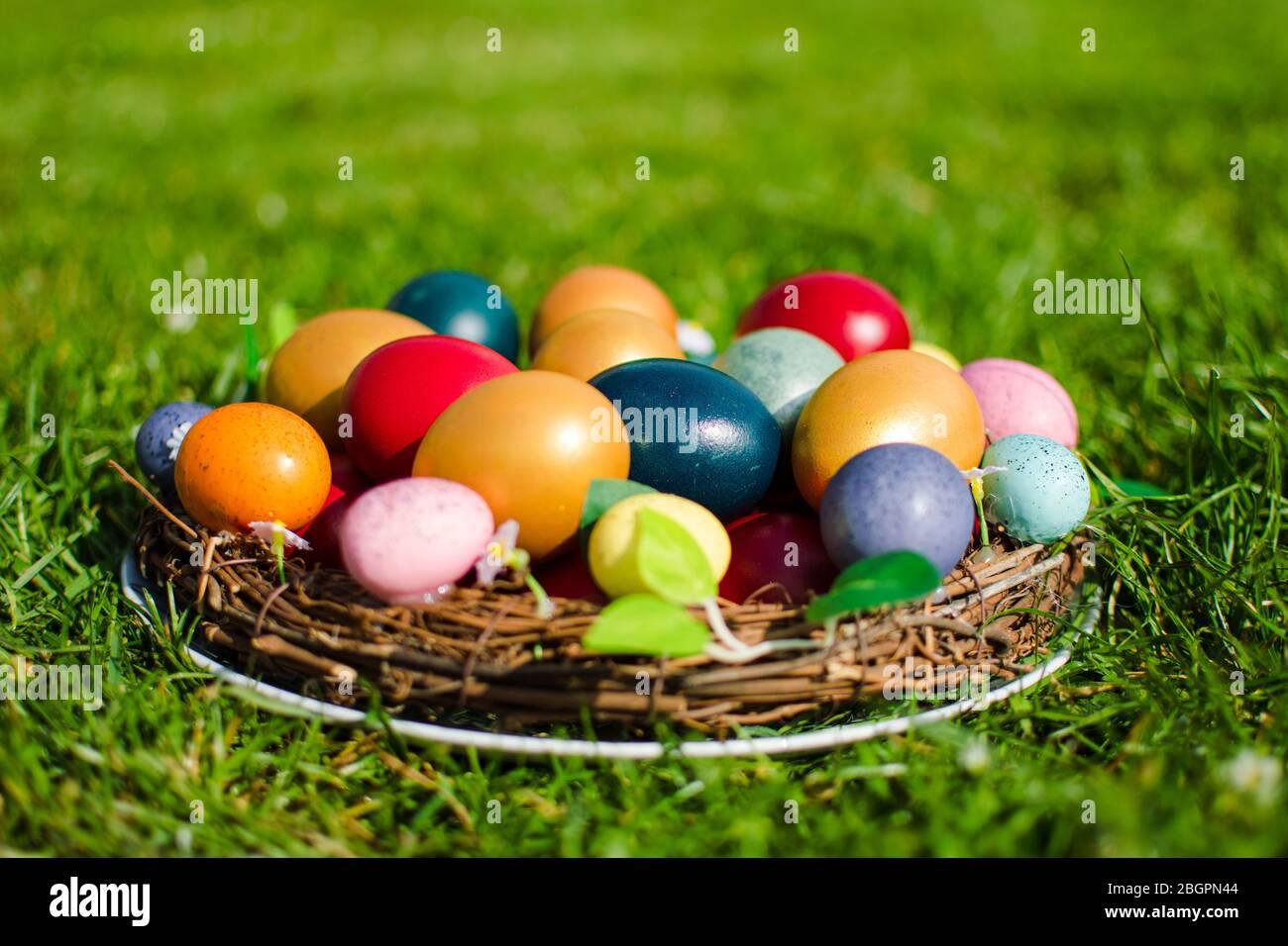 Stock photo des oeufs de Pâques dans un panier en bois sur l'herbe verte comme symbole de Pâques dans la religion chrétienne. Banque D'Images