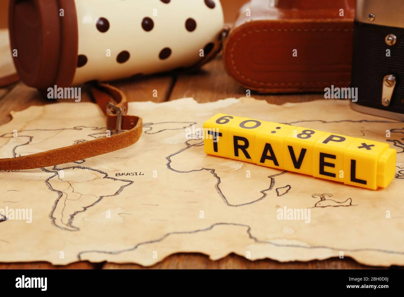 Caméra rétro sur la carte du monde avec mot Voyage sur fond de table en bois Banque D'Images