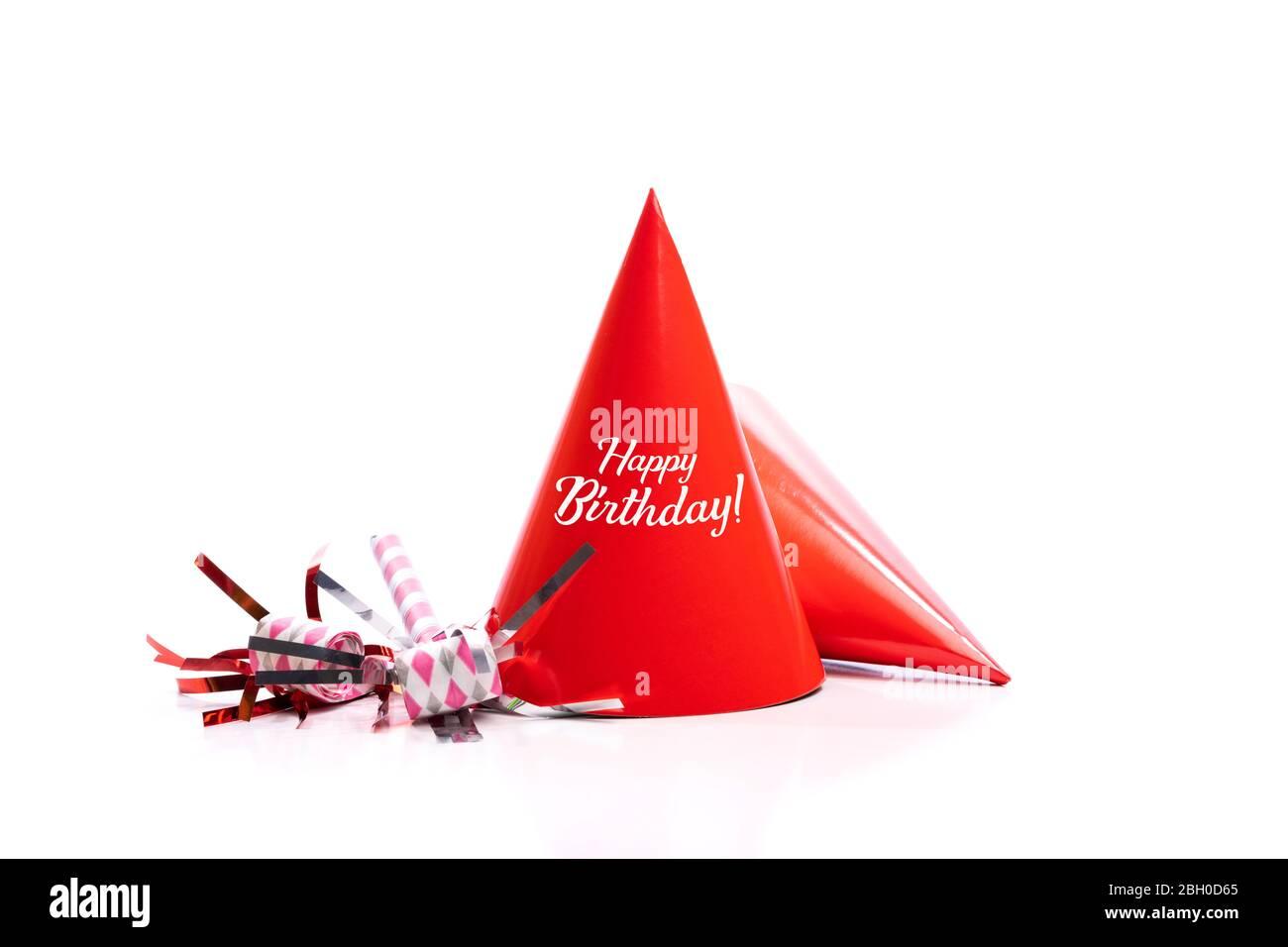 Chapeaux d'anniversaire rouges et appareils de bruit sur fond blanc. Banque D'Images