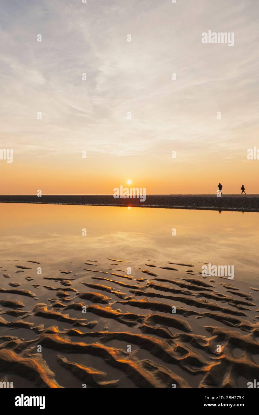 Vue lointaine de silhouette personnes marchant à la plage contre le ciel pendant le coucher du soleil, côte de la mer du Nord, Flandre, Belgique Banque D'Images
