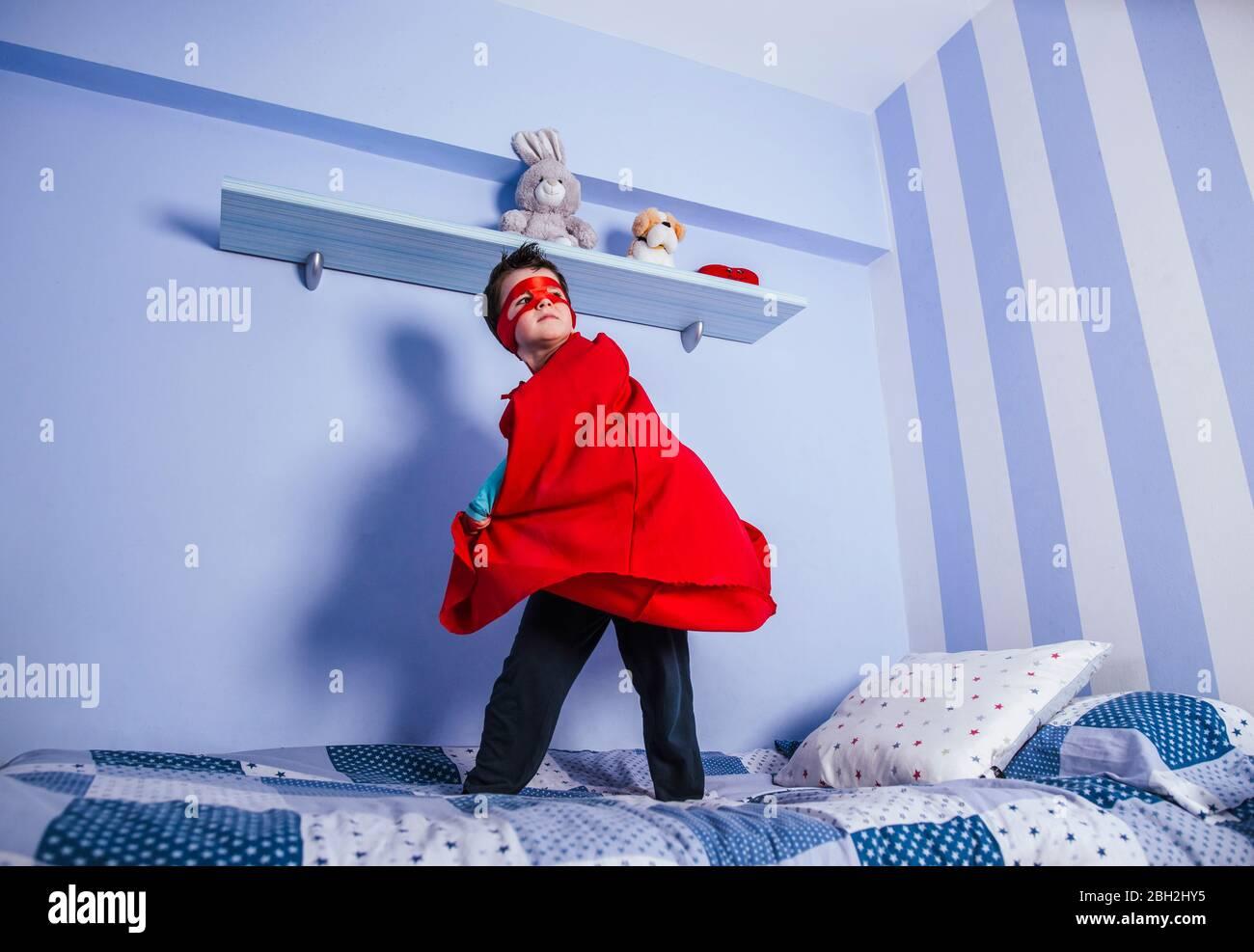 Petit garçon jouant super héros, debout sur son lit Banque D'Images