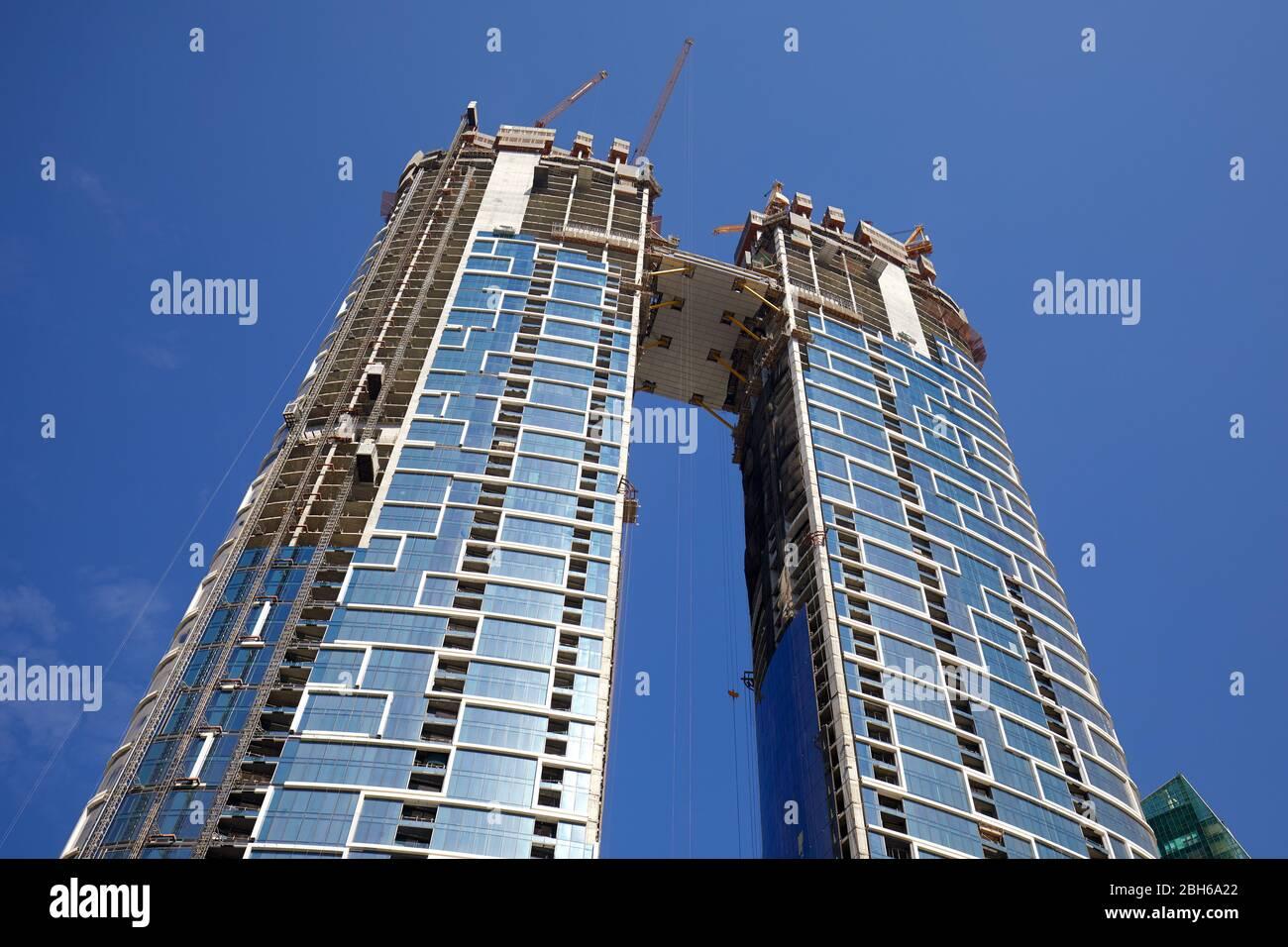 DUBAÏ, EMIRATS ARABES UNIS - 23 NOVEMBRE 2019: Gratte-ciel en construction avec grues, vue à angle bas en journée ensoleillée, ciel bleu clair à Dubaï Banque D'Images