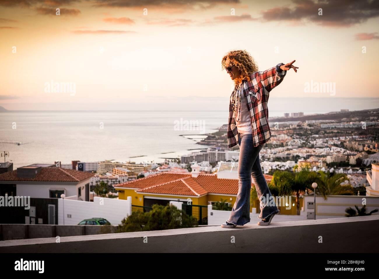 Femme souriante se promenant dans l'équilibre sur une belle vue sur la côte de la ville au coucher du soleil - liberté et indépendance concept de bonheur pour les personnes d'âge moyen profitant d'activités de loisirs en plein air sur les maisons Banque D'Images