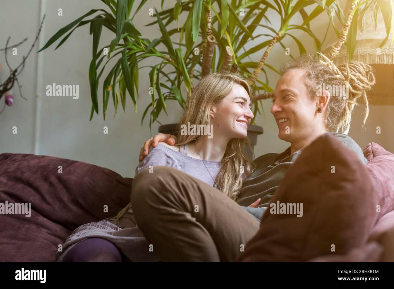 Un jeune couple moderne et affectueux avec des verrous de lit assis bras sur un canapé riant et regardant dans les yeux des autres Banque D'Images