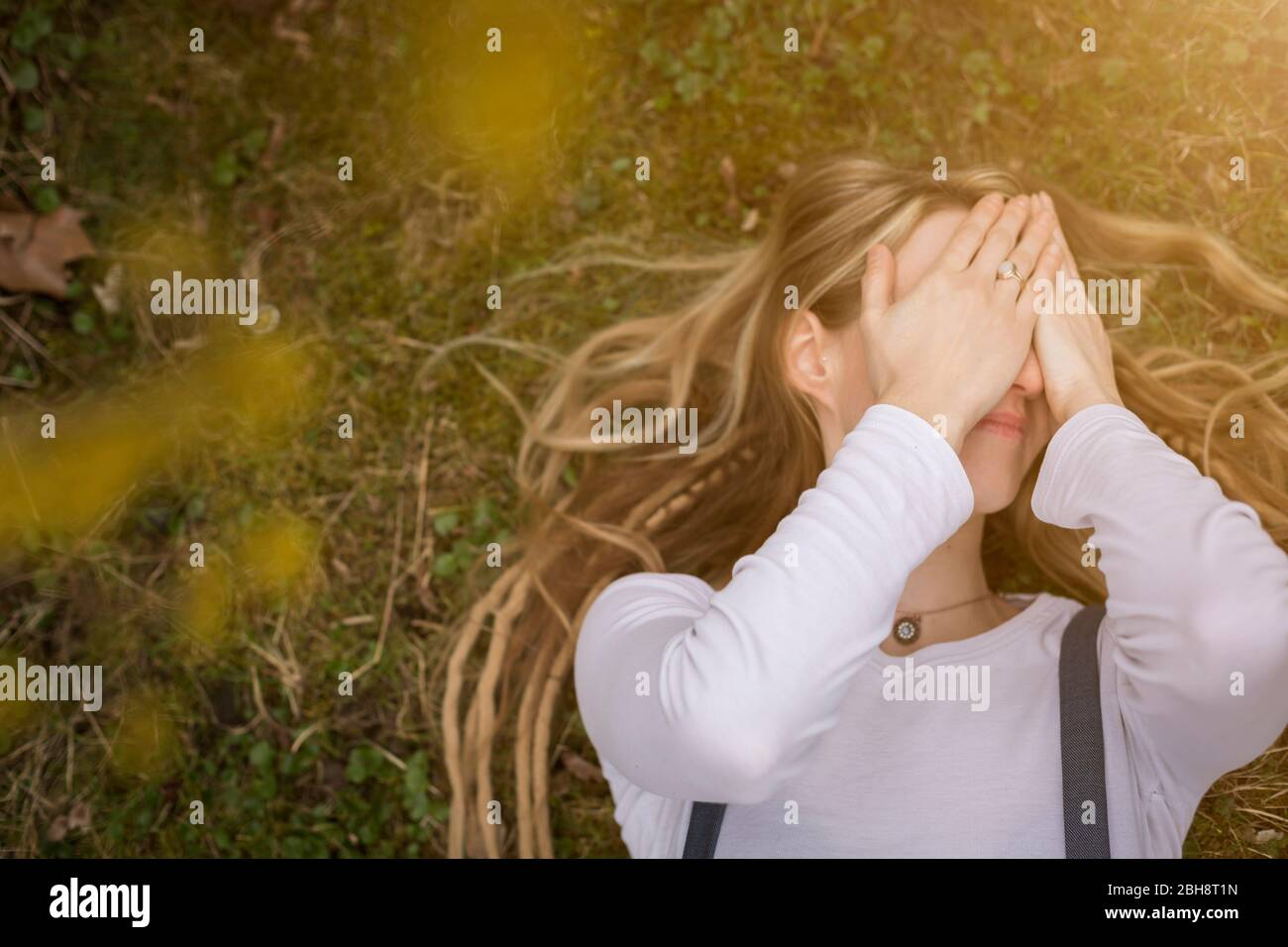 Portrait rapproché d'une jeune femme blonde heureuse tenant des readlocks à genoux tenant une fleur jaune dans un jardin de printemps Banque D'Images