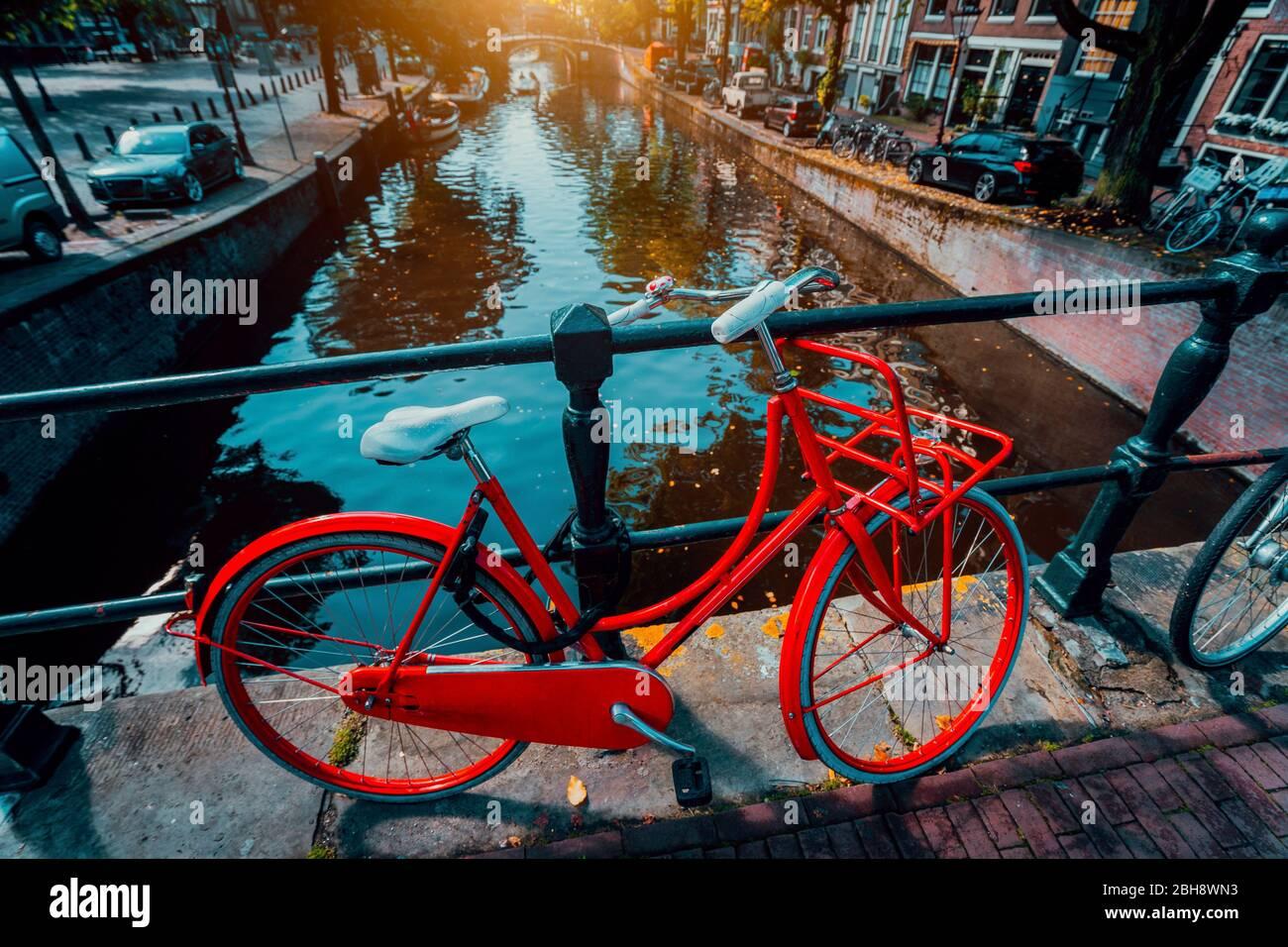 Symboles d'Amsterdam: Vélo rouge garée sur un pont, aux Pays-Bas. Romance, voyage, vacances. Concept de culture Banque D'Images
