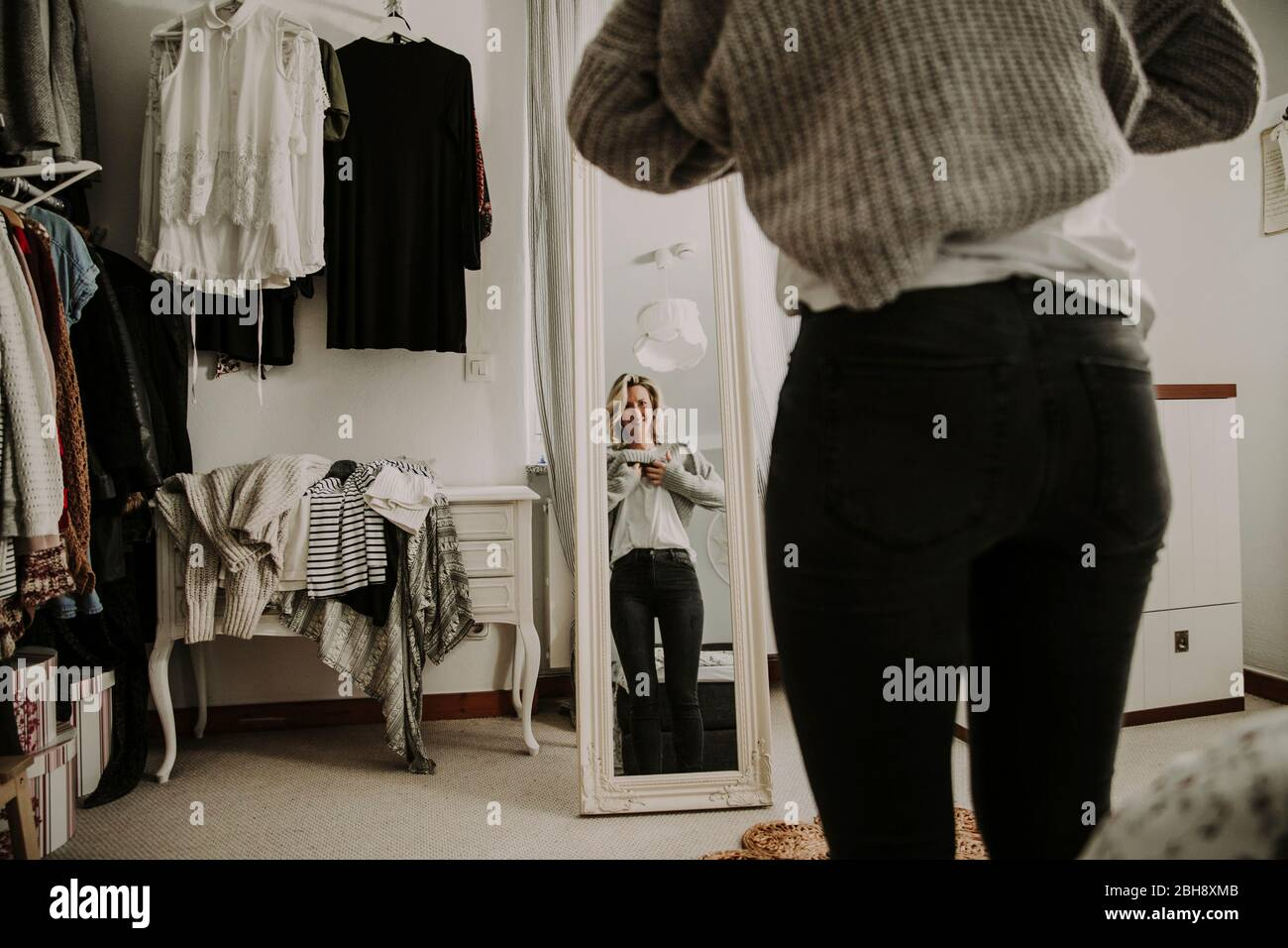 Femme se tient devant le miroir, robes Banque D'Images
