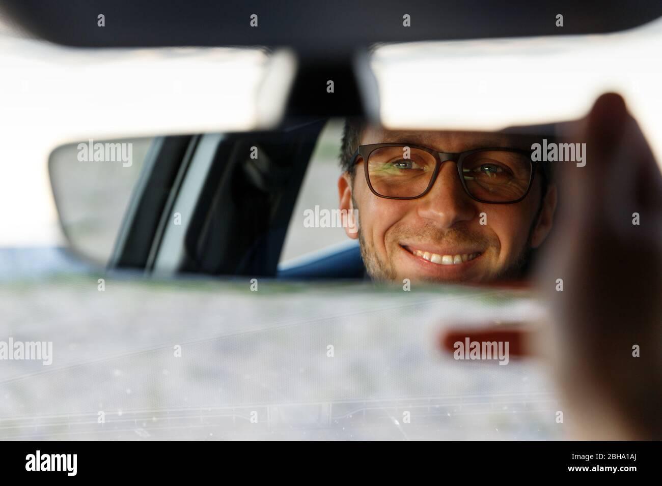 Homme joyeux et joyeux portant des lunettes et un miroir de réglage tout en étant assis dans sa voiture, regardant en réflexion. Mise au point douce. Émotions de conduire une nouvelle voiture Banque D'Images