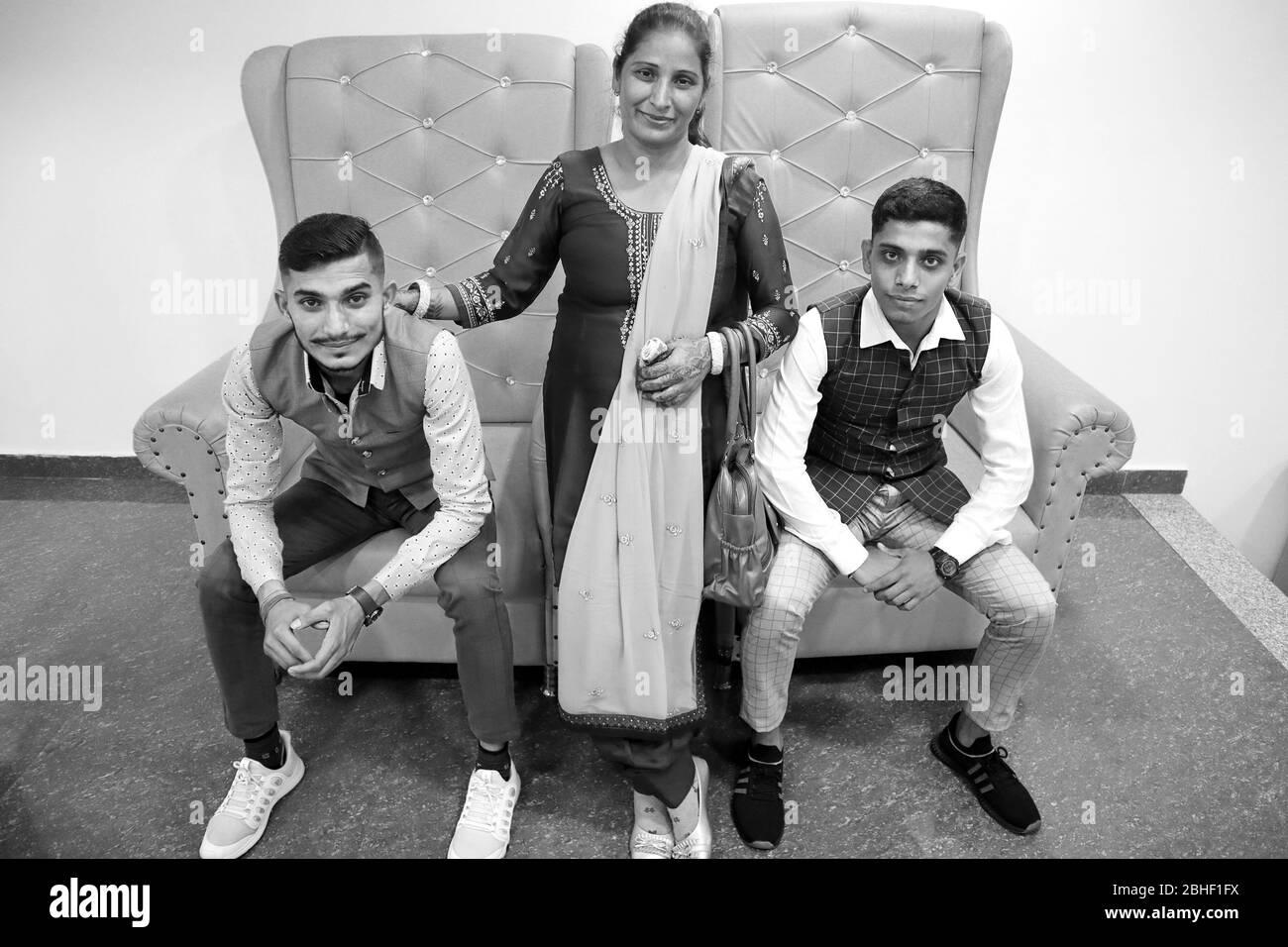 Portrait de famille à la maison sur le canapé. Jeune mère avec ses deux jeunes fils et ils regardent tous la caméra Banque D'Images