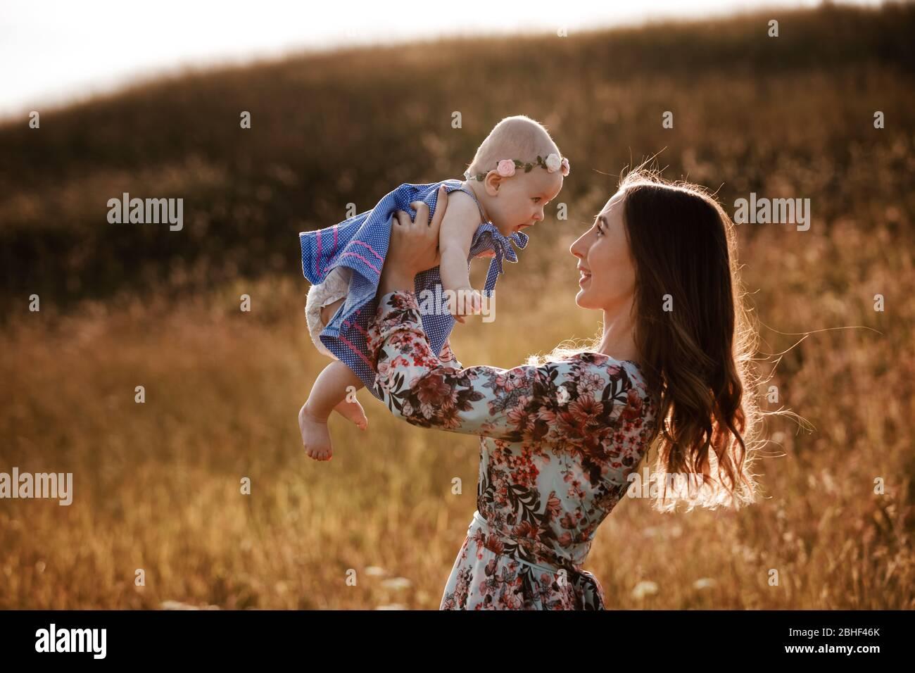 Belle femme lève haut son adorable fille de bébé en plein air et regarde son sourire. Joyeux parent passer du temps à jouer avec sa fille dans le parc à Banque D'Images