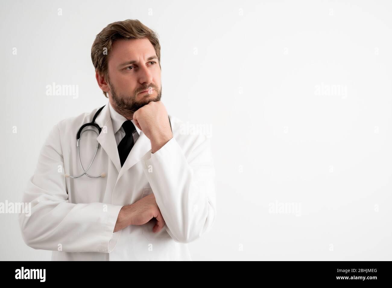 Portrait d'un médecin mâle avec stéthoscope en uniforme médical tenant la main sous son menton, ayant douté poser sur un fond blanc isolé Banque D'Images
