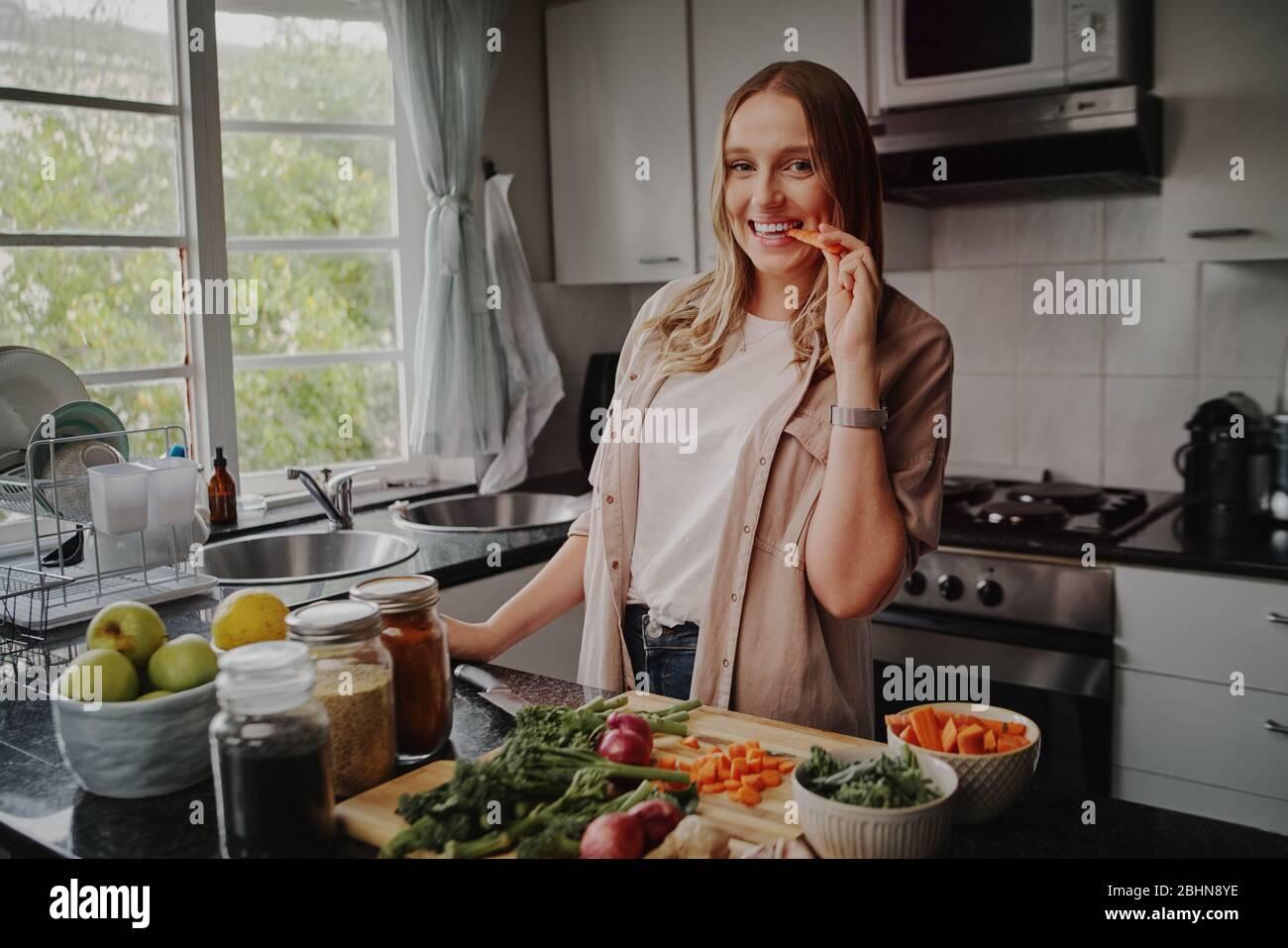 Jeune femme gaie dans la cuisine moderne préparant salade de légumes frais et manger une carotte souriant à l'appareil photo Banque D'Images