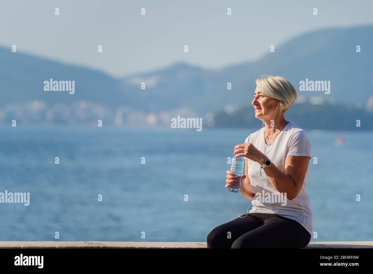 Femme mûre buvant de l'eau après le jogging sur fond de la mer et du ciel bleu Banque D'Images
