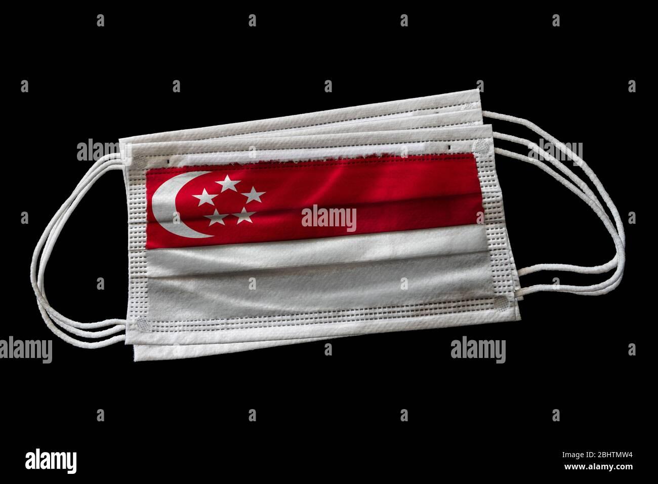 Masques chirurgicaux avec drapeau de Singapour imprimé. Isolé sur fond noir. Concept d'utilisation de masque de visage dans l'effort singapourien pour combattre Covid-19 cor Banque D'Images