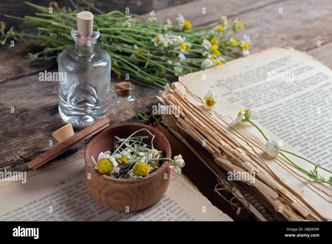 Vieux livre avec fleurs sèches dans mortier sur table près Banque D'Images