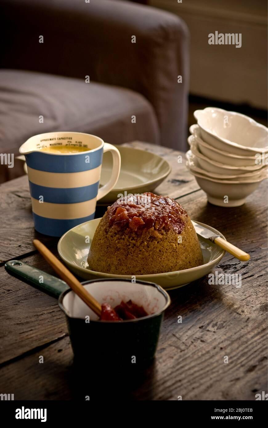 Pudding éponge traditionnelle à la vapeur avec des morses et compote de rhubarbe et crème anglaise, servi dans un cadre informel - Banque D'Images