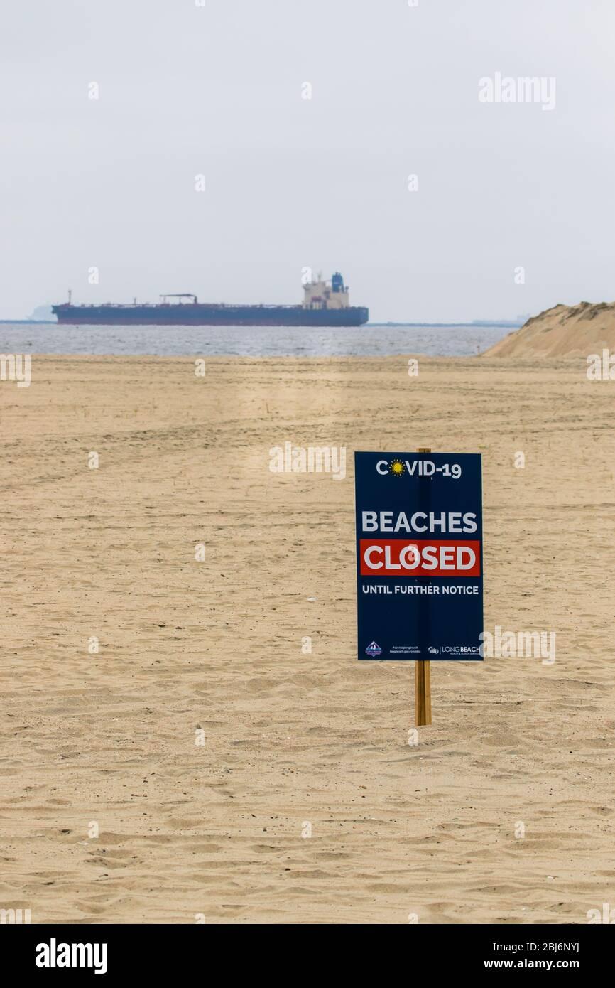 Plage fermée Covid19 panneaux avec des pétroliers ancrés au large de la côte de long Beach, Californie du Sud; États-Unis. Banque D'Images