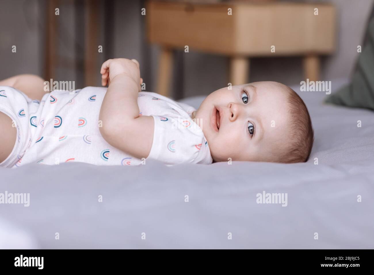 portrait de la petite fille mignonne de bébé se trouve sur le lit dans la chambre à la maison. concept de bonne enfance Banque D'Images