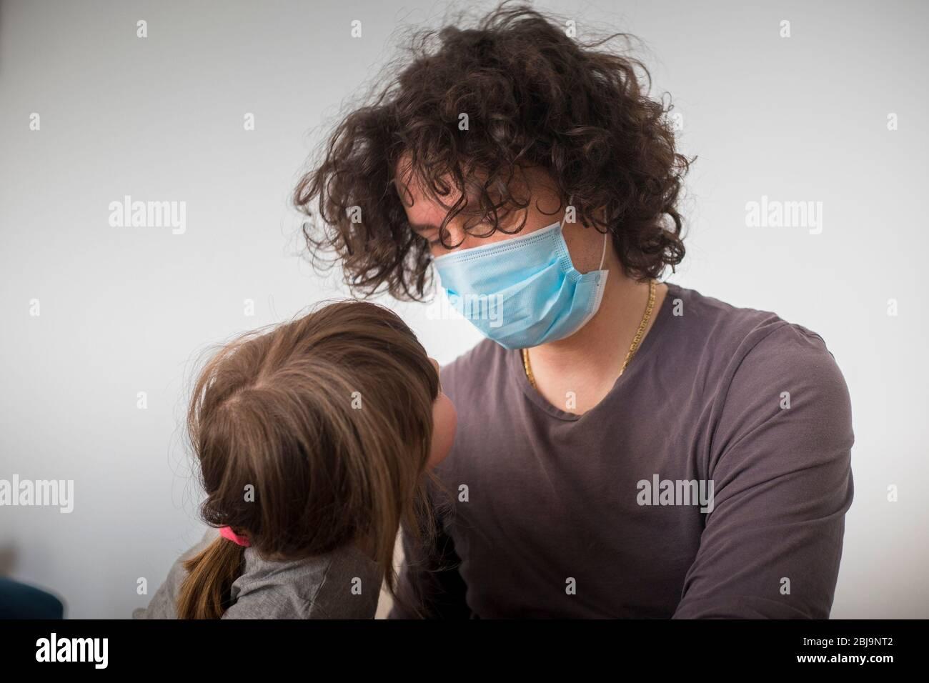 Père caucasien, portant un masque facial pour éviter la contagion, plaisantant avec la fille d'enfant pendant le verrouillage de la pandémie de covid-19. Papa et fille de bébé à la vue proche. Banque D'Images