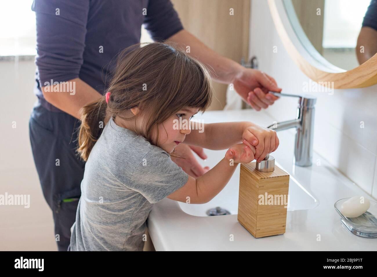 Père caucasien enseignant à la petite fille d'enfant comment se laver les mains dans la salle de bains pendant le verrouillage de la pandémie covid-19. Papa et fille de bébé se laver les mains à si Banque D'Images