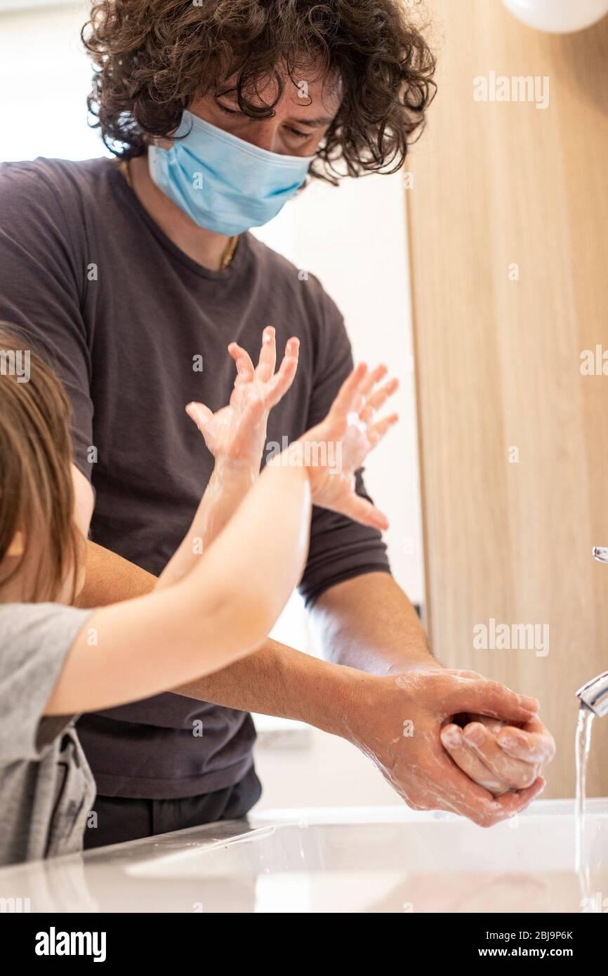 Le père caucasien porte un masque facial pour éviter la contagion enseignant à la petite fille d'enfant comment se laver les mains dans la salle de bains pendant le verrouillage de la pandémie de covid-19. Père Banque D'Images