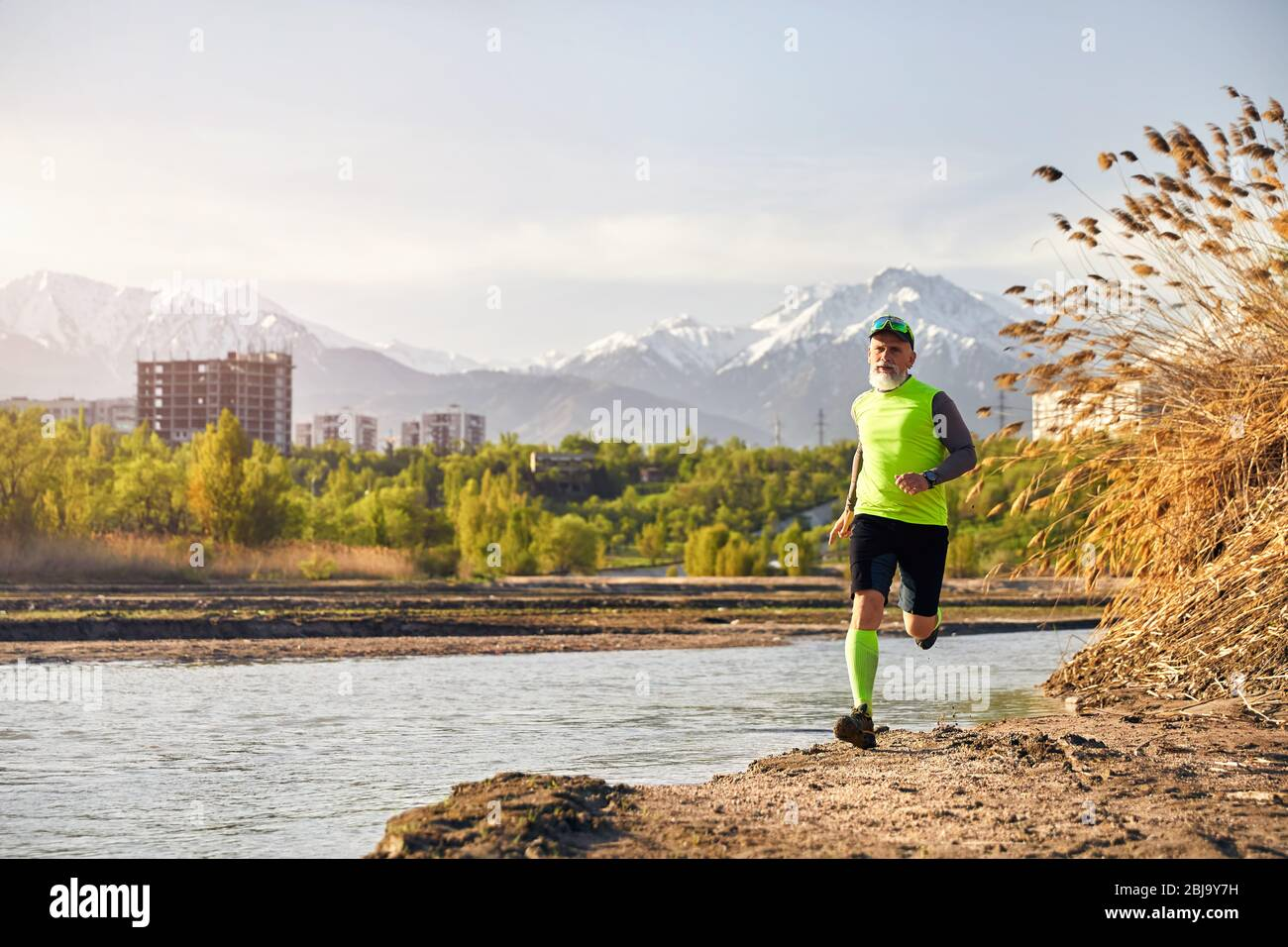 Homme à barbe grise en marche près du lac avec en arrière-plan la montagne le matin. Concept de vie sain Banque D'Images